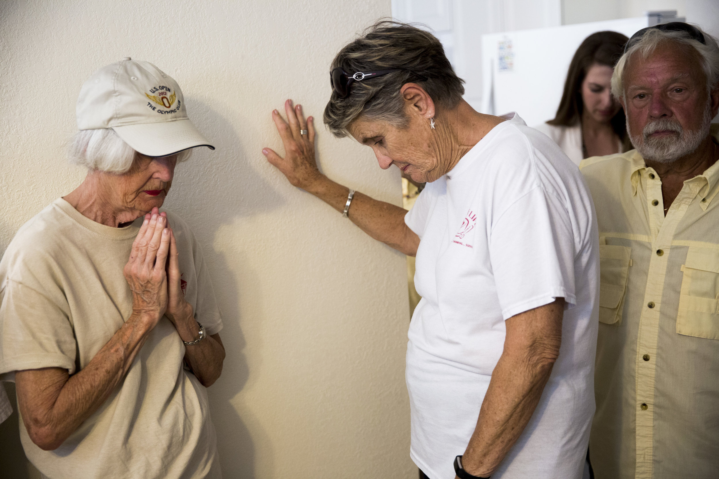 Habitat for Humanity volunteers, in a moment of prayer, place their hands on one of the recently donated homes during the dedication process Friday, April 13, 2018 in Bonita Springs, Fla.