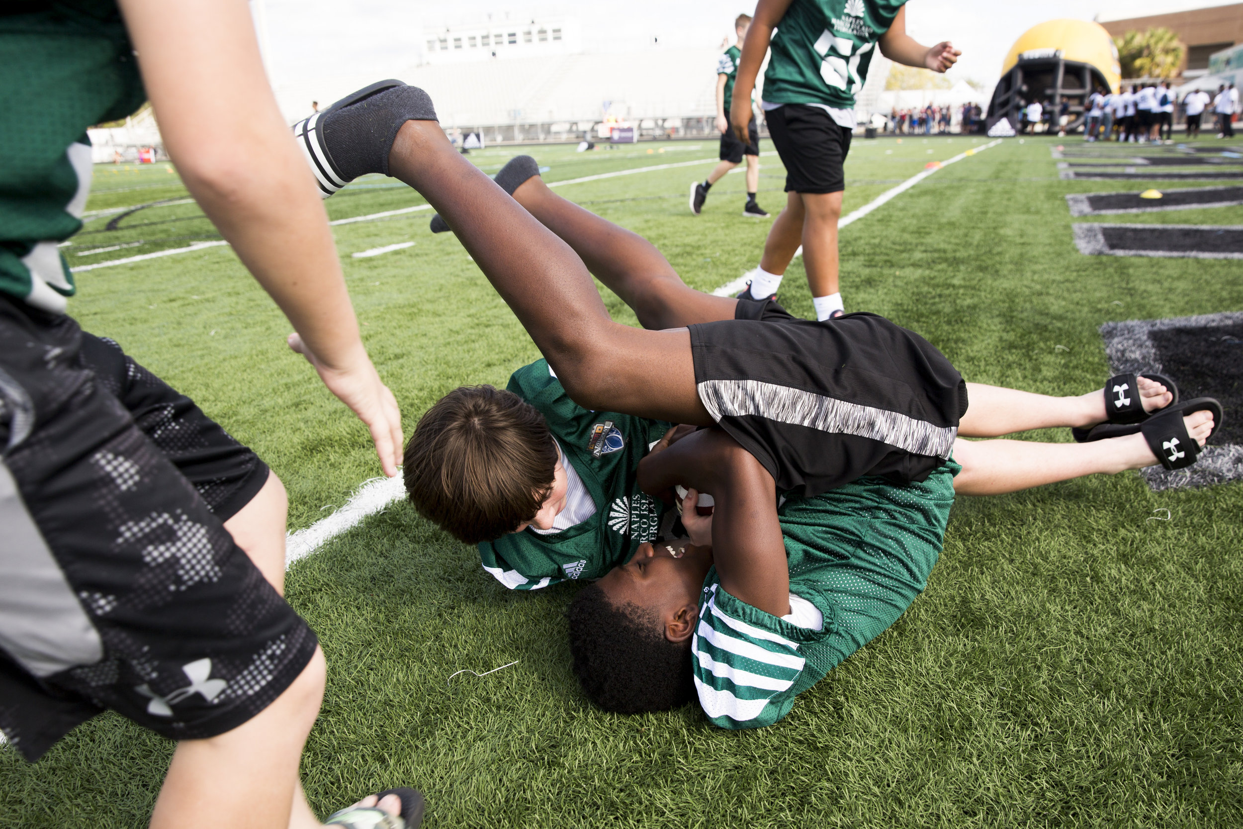 James Johnson, 12, does a somersault while wrestling for the ball with Dane Aaberg, 12, both with the 6th Grade team from Dallas, Texas as middle-school football players from across the country showed up for registration and a pep rally to kick off the FBU National Championships at Gulf Coast High School Sunday, Dec. 17, 2017 in Naples, Fla.