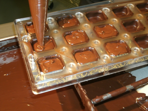 Piping in the ganache filling for some delicious chocolate truffles!