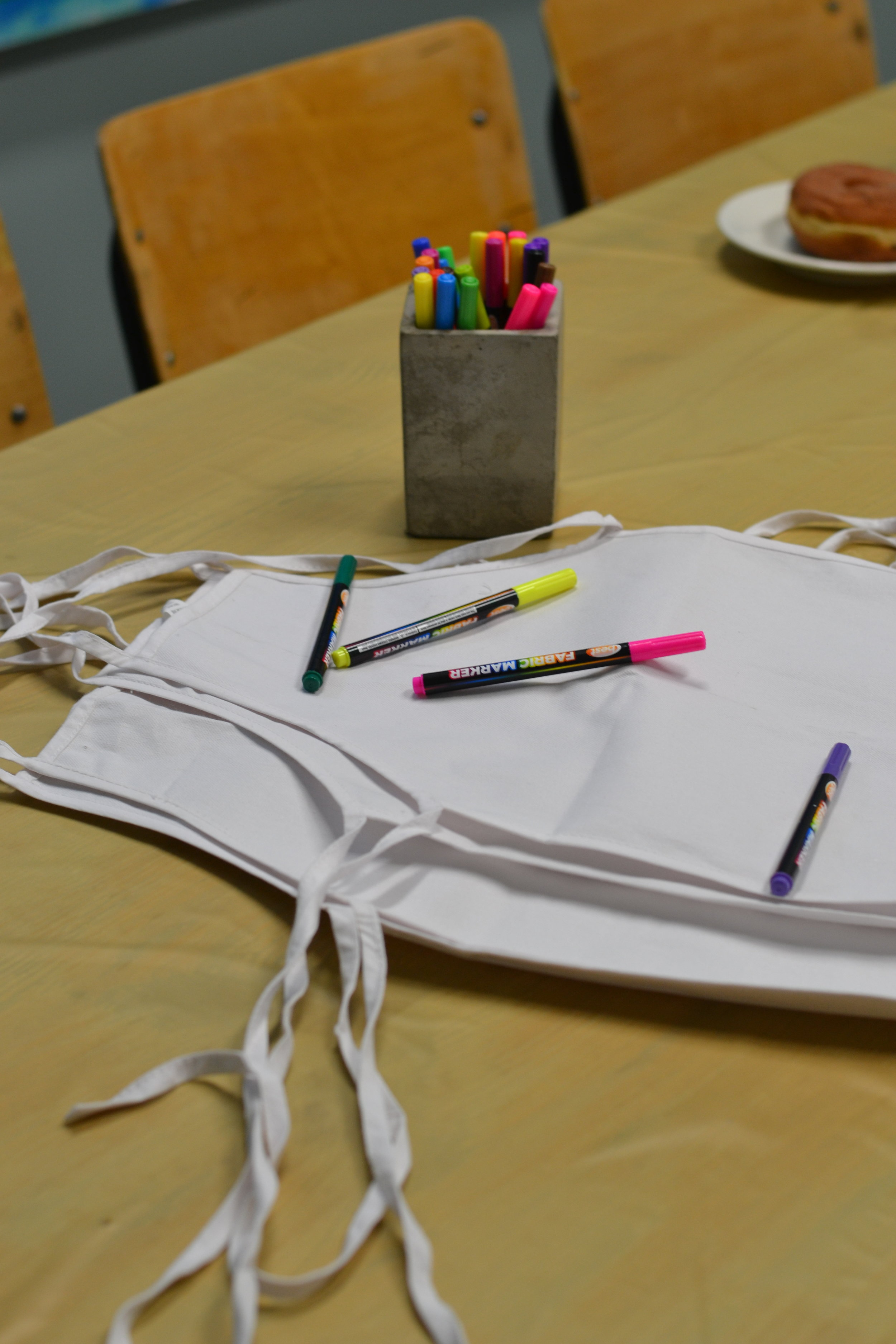 Decorate your own aprons, complete with fabric markers