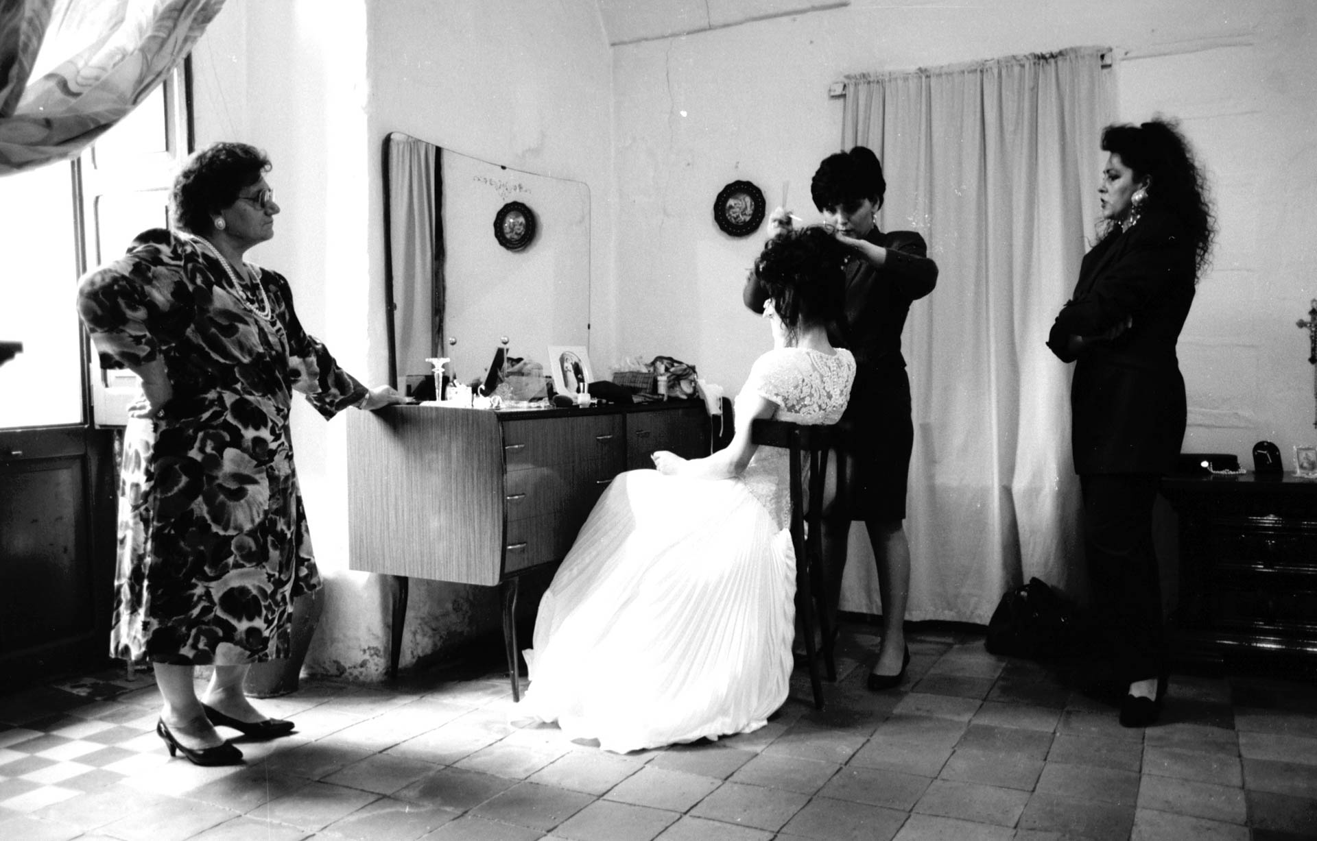 Matera, Italy - 19 October 1991 Preparation and dressing of the bride, assisted by the bride's maids.
