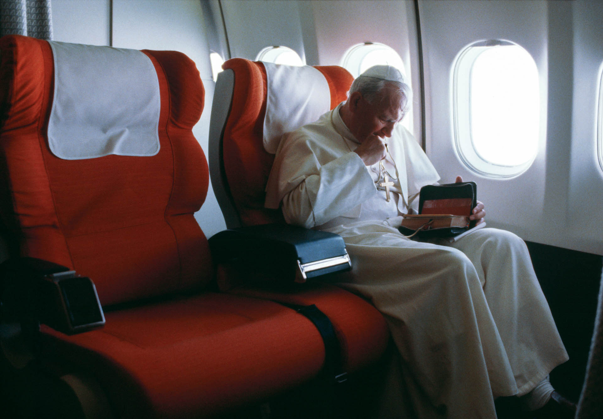 Argentina - June 1982 Pope John Paul II takes few moments to read the breviary in the special area prepared for him on long flights. Here coming back from Argentina.