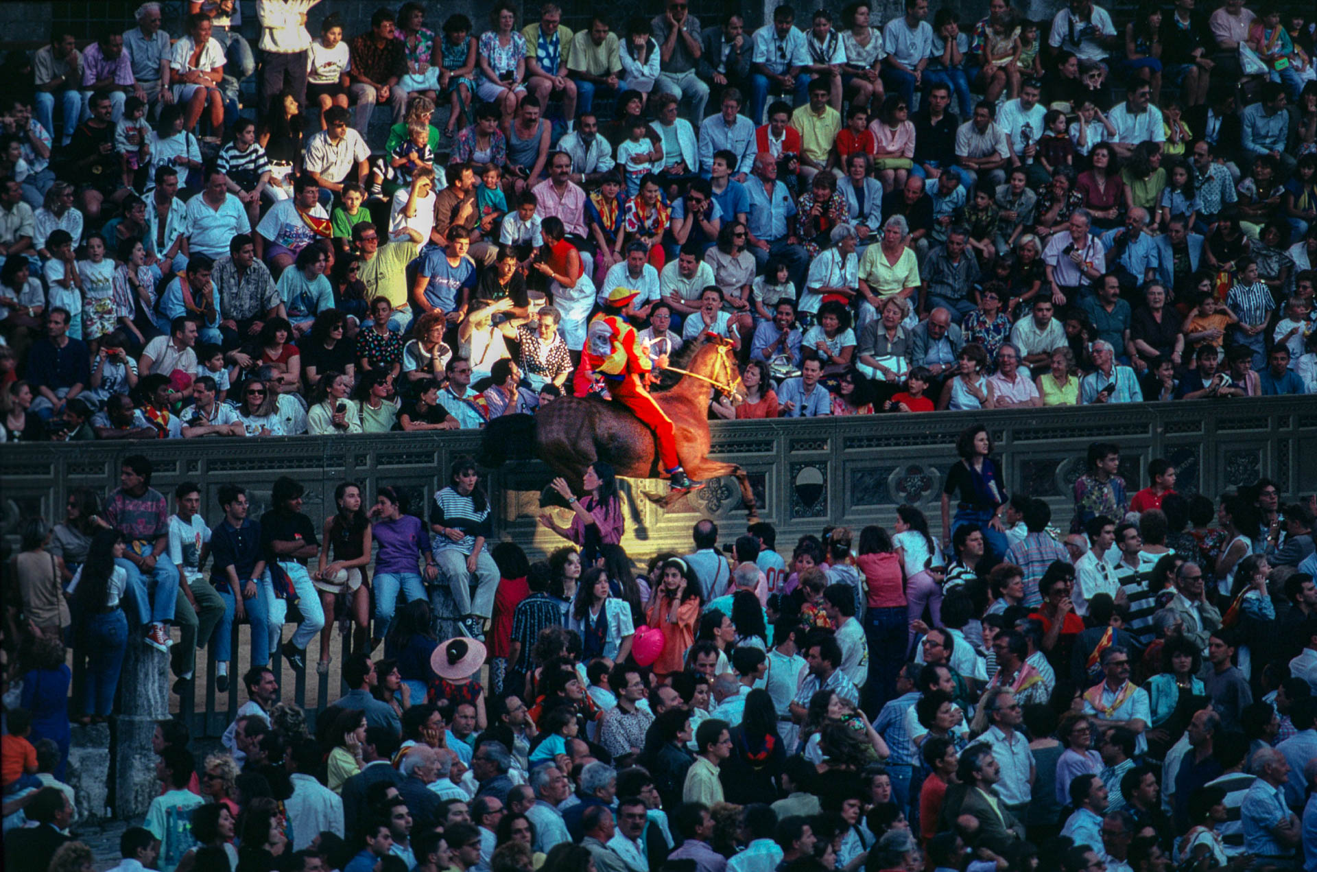 Siena, 1 July 1991 During the final trials, a jockey rides among the crowd waiting for the start of the Palio.
