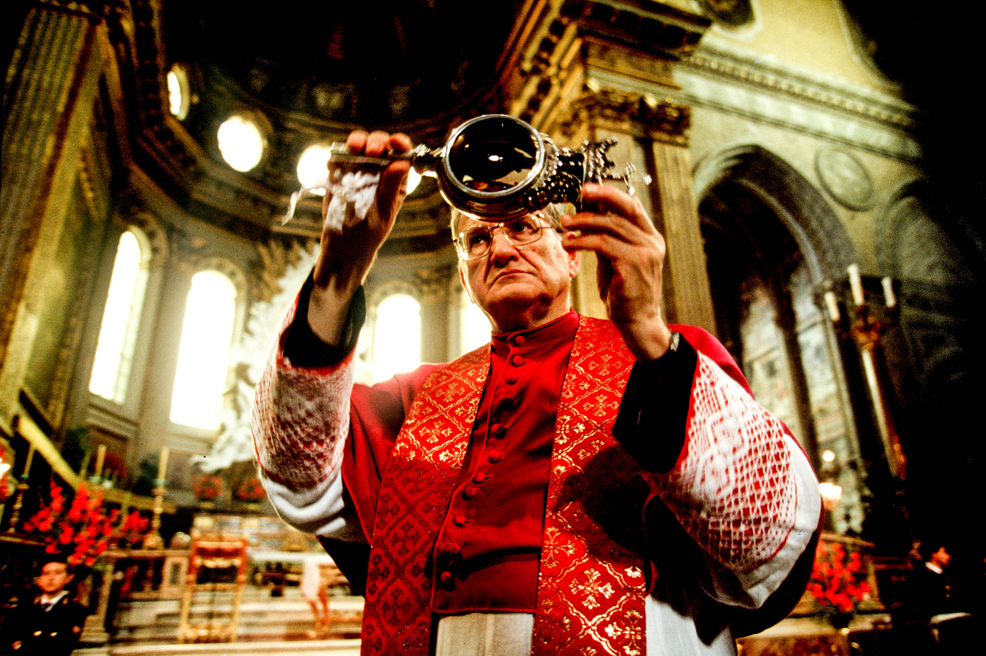 The miracle around the world: the bishop displays to the believers the blood of a saint.