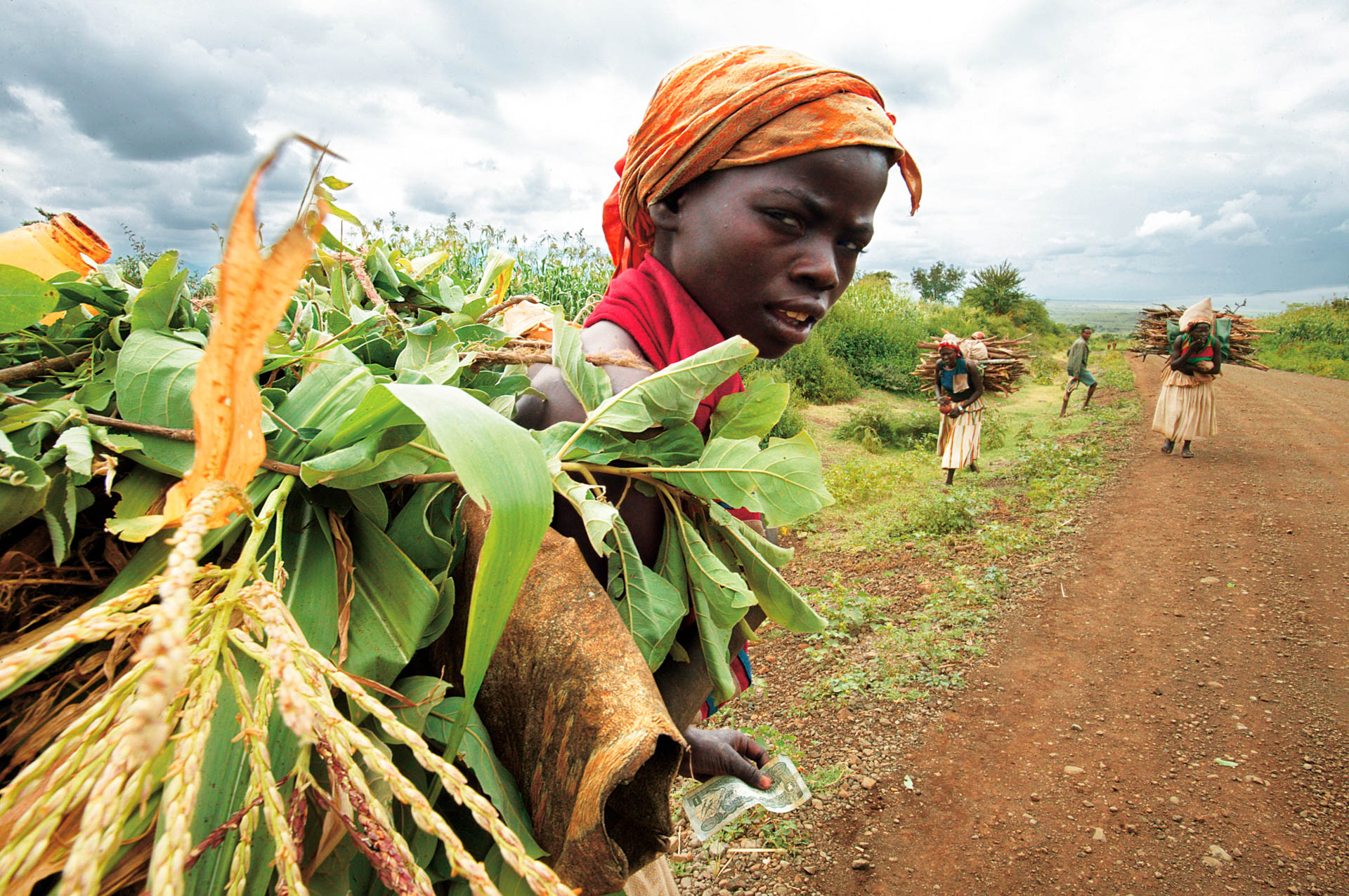 Fatigued by her heavy load, a girl stops to rest on the road leading to the market.