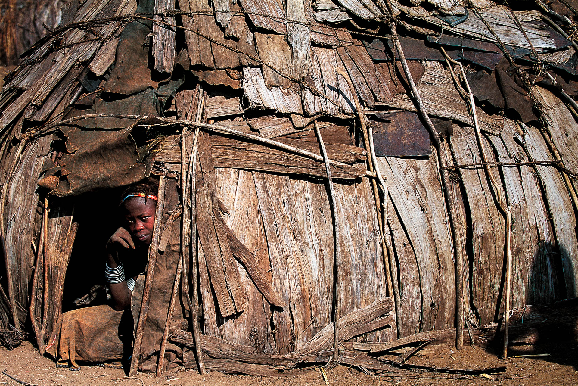 At Rate the children find shade in the huts.