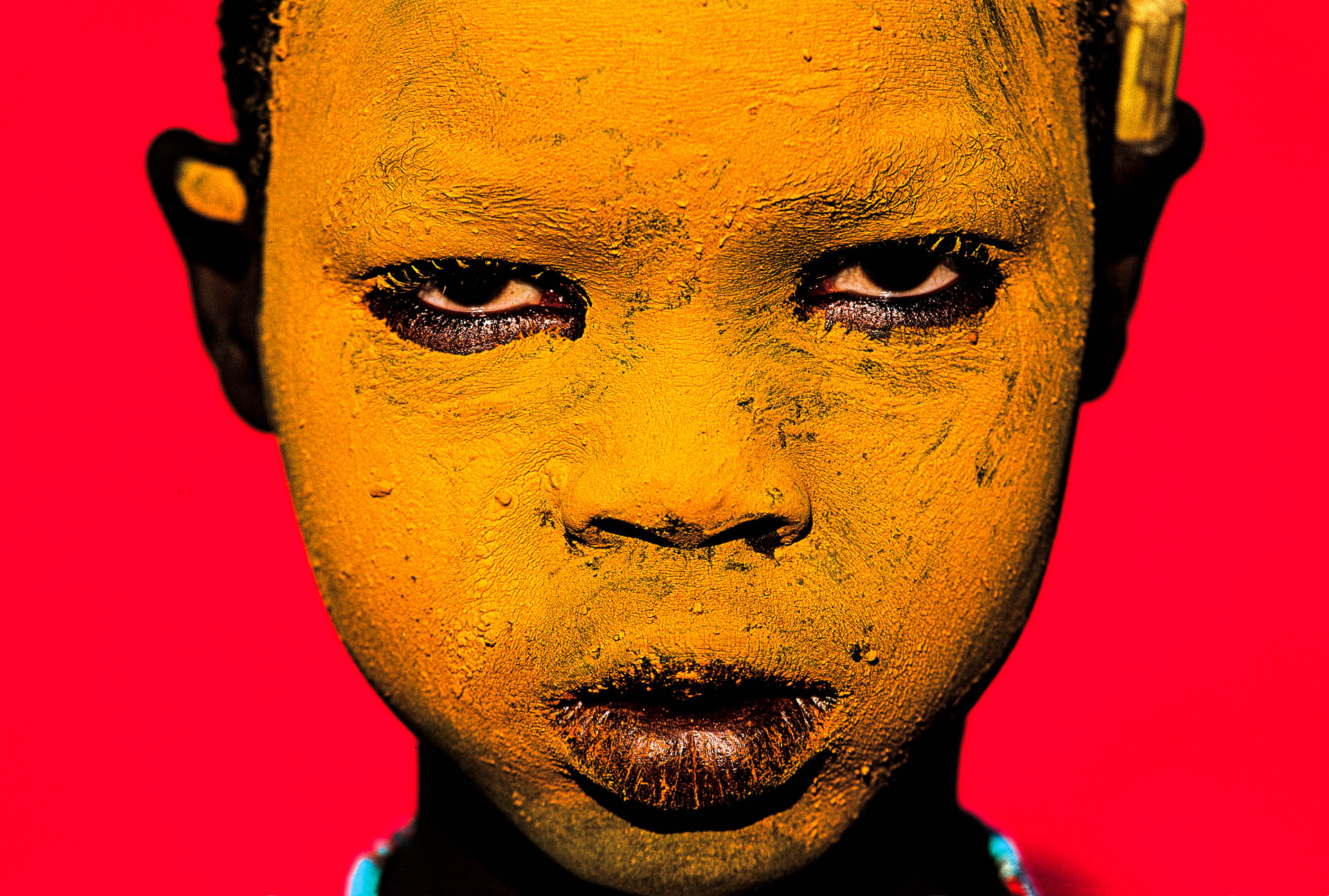 A Surma child, whose face is painted yellow, poses for the photographer.