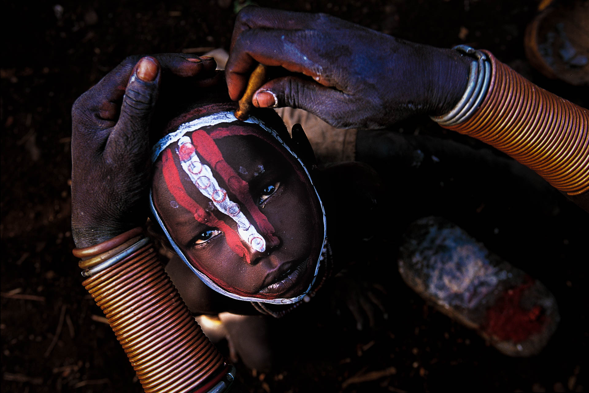 Ghere Kara, the village expert, meticulously paints a child's face using a cartridge case as a brush.