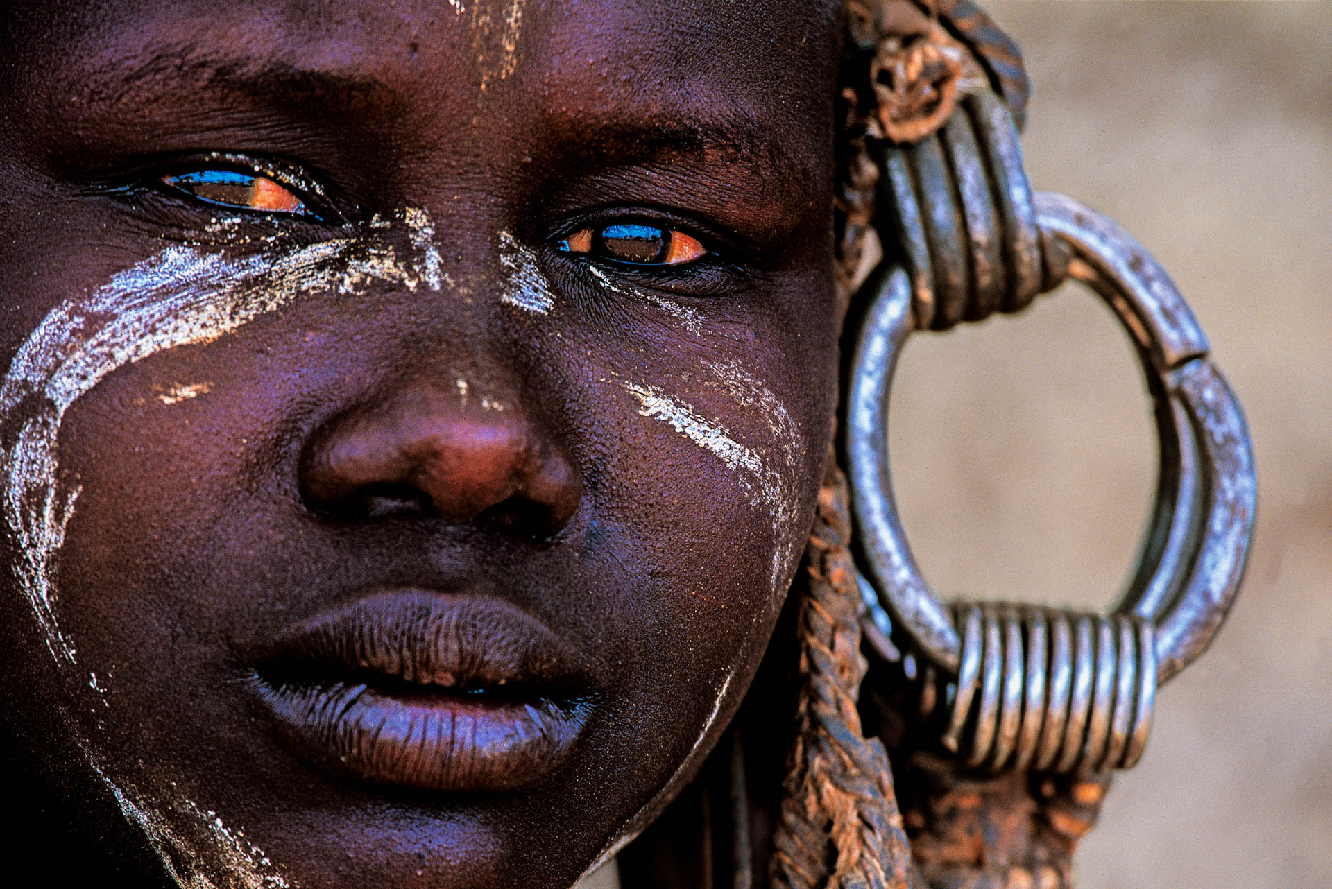 A little girl wearing gaudy and heavy round iron earrings.