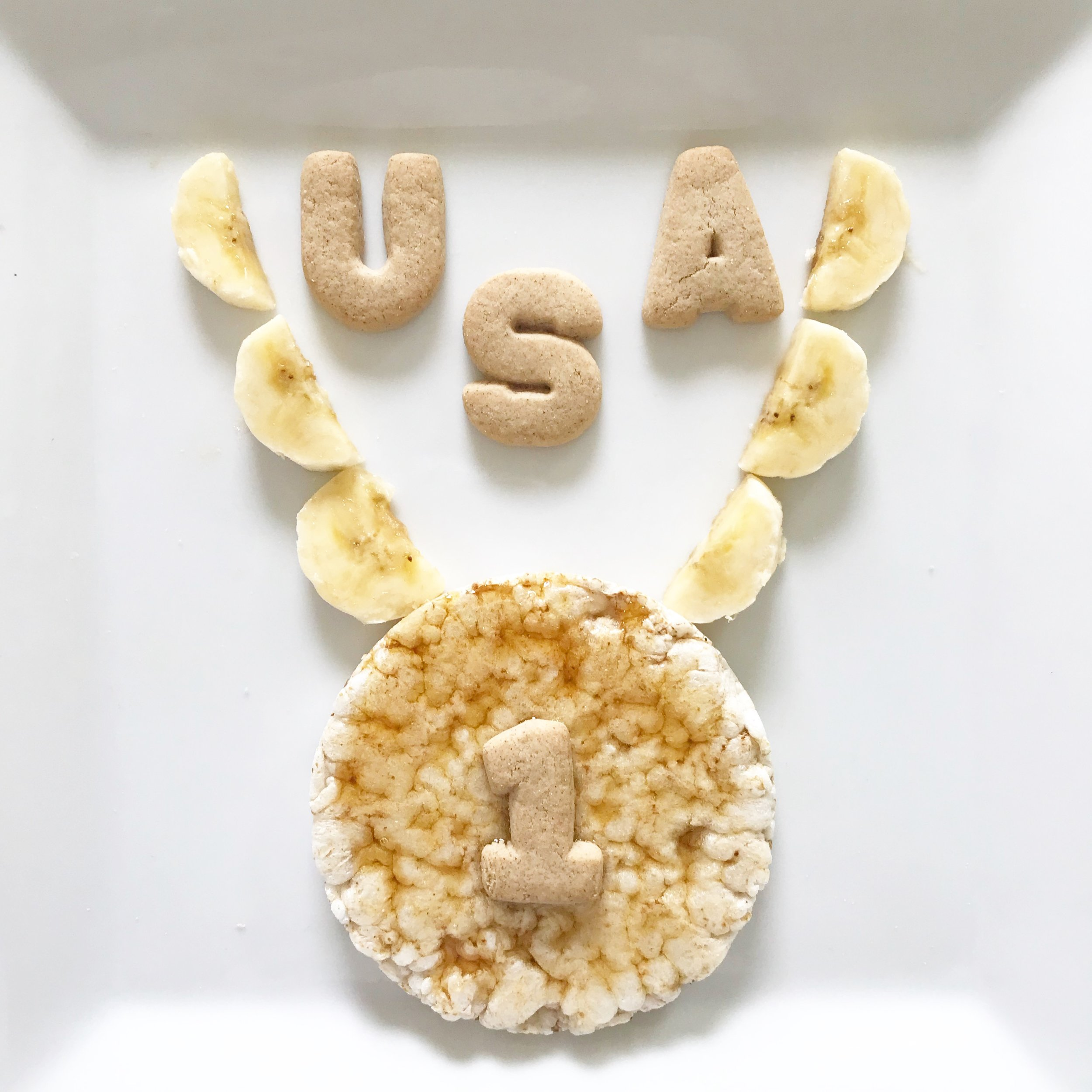 + Rice cake + honey (to make it gold)  +Sliced banana for necklace  + Number cookies for #1 + Letter cookies for USA