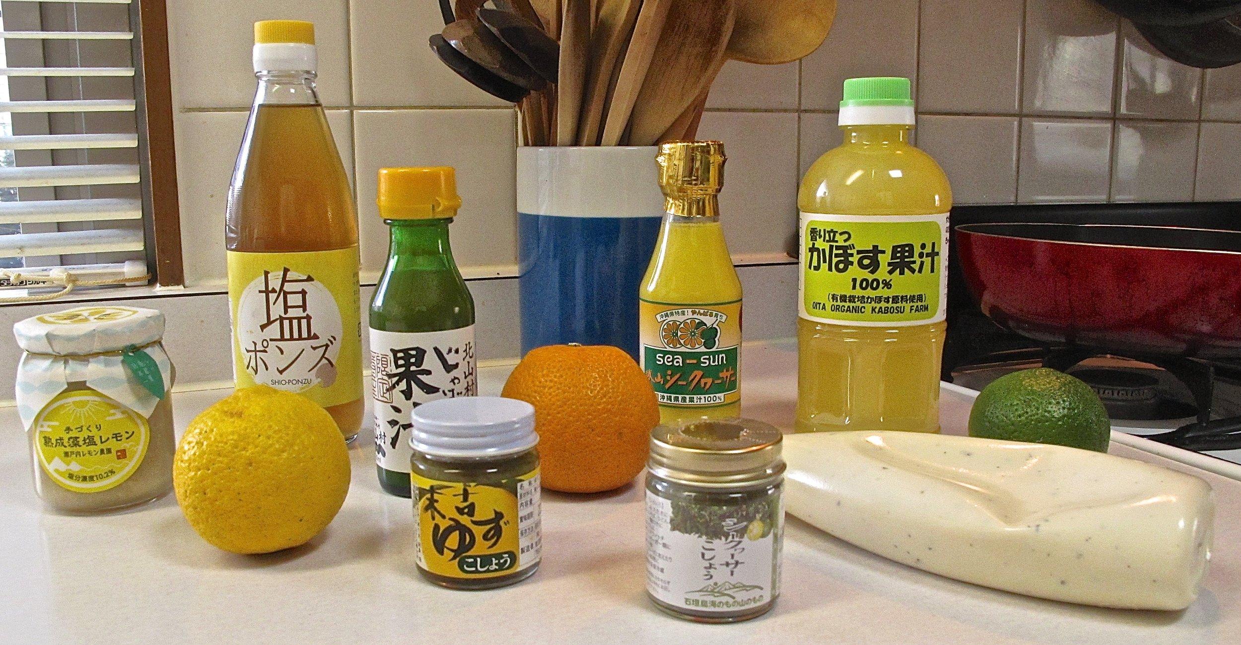 Back left to right:  shio-ponzu  made from sea salt and lemon juice, bottled  jabara  juice, fresh  jabara , bottled  shikwasa  juice, bottled  kabosu  juice, and fresh  kabosu . Front left to right:  shio-lemon  a fermented paste made from sea salt and mashed lemons, fresh lemon, small jar of  yuzu kosho , small jar of  shikwasa kosho , and  kabosu  mayonnaise.