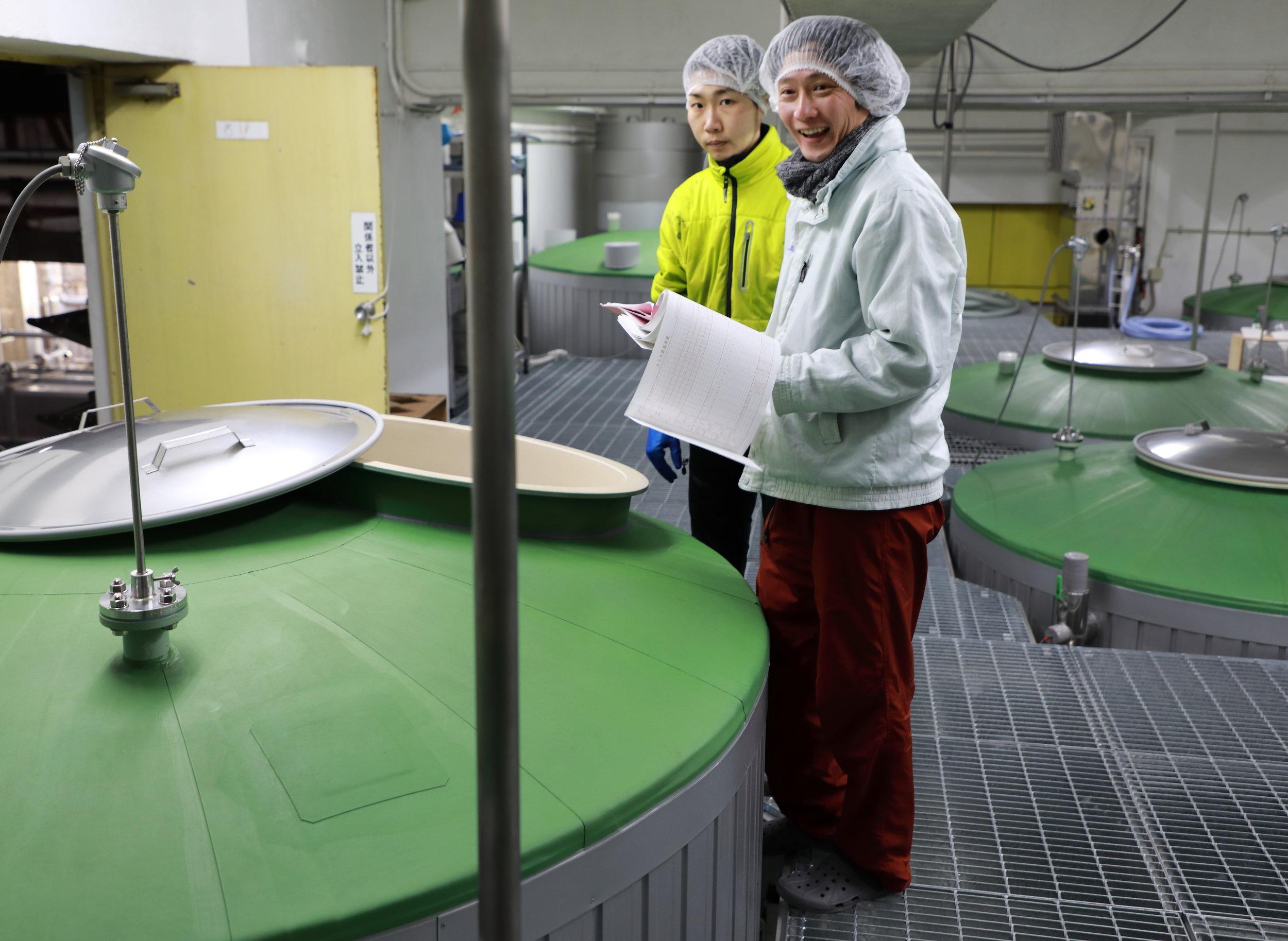 Kazuma Matsuzawa, standing on the right in the main fermentation room, is Yucho Shuzo's  toji , or chief brewer. Like Yoshi, Kazuma is 35 years old and was trained by Yoshi's father, Chobei Yamamoto.