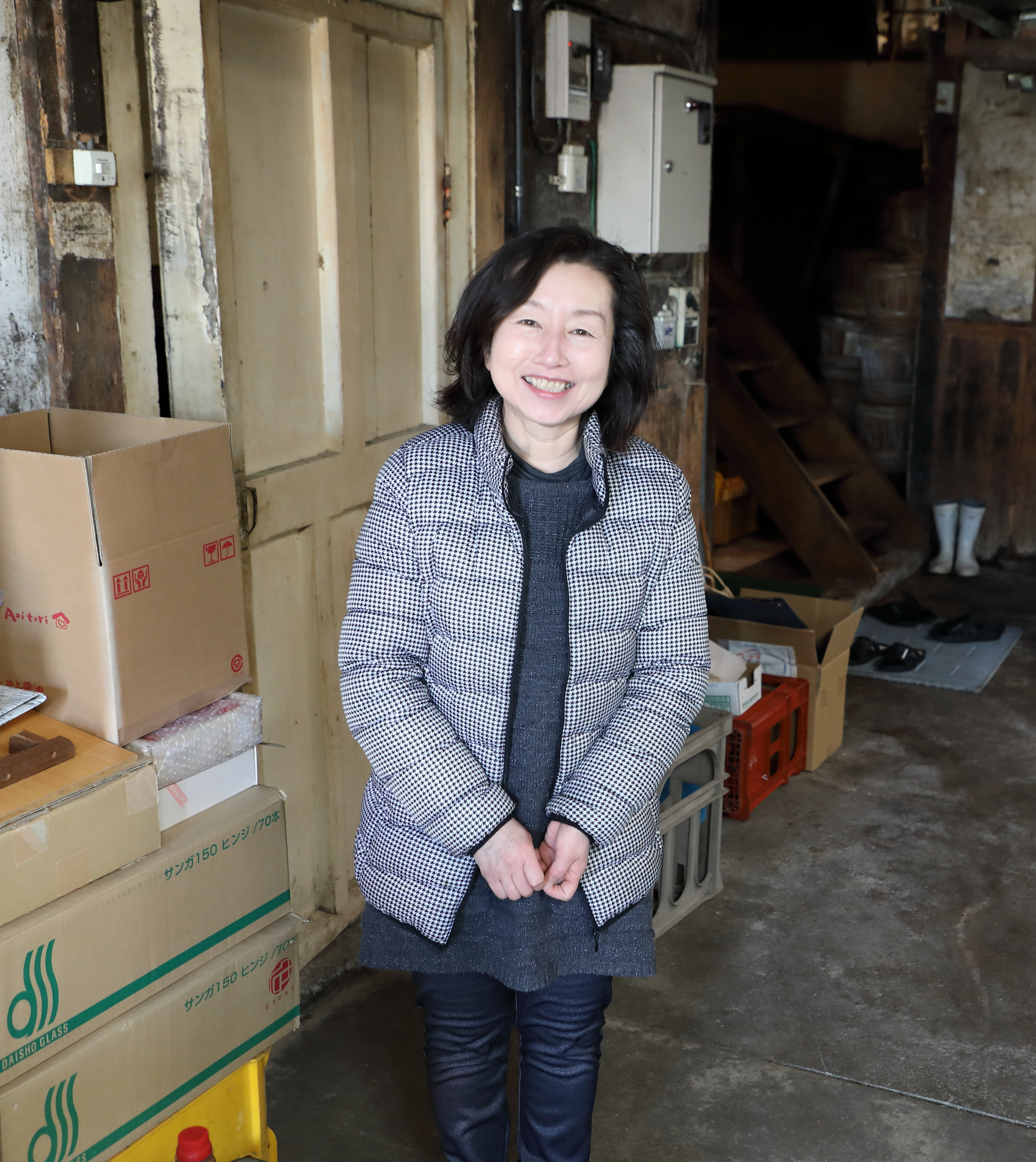 Mrs. Katakami standing in front of the door to the  muro , the room in which the fermentation process begins with the cultivation of soy sauce  koji .