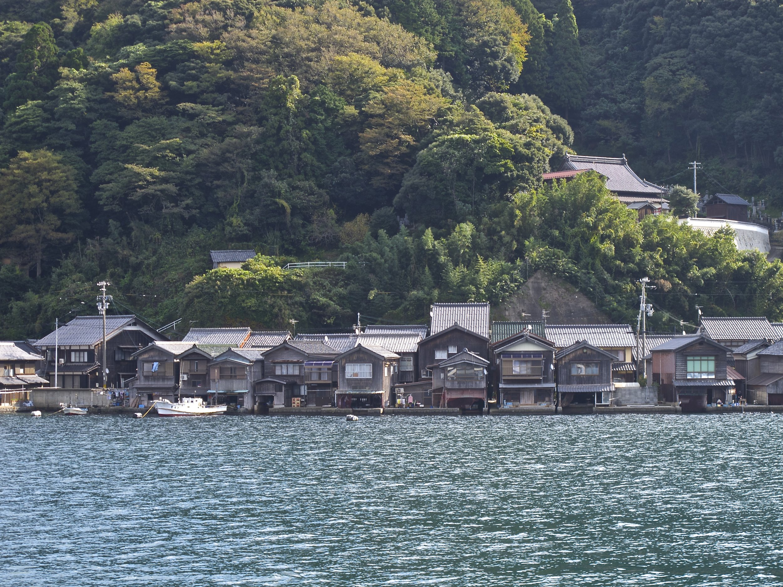 The  funaya  of Ine seen from the water. In the past, only the village's Shinto shrines and Buddhist temples, like the one pictured on the hill on the right, were built into the sides of the surrounding mountains because the mountains were considered sacred.