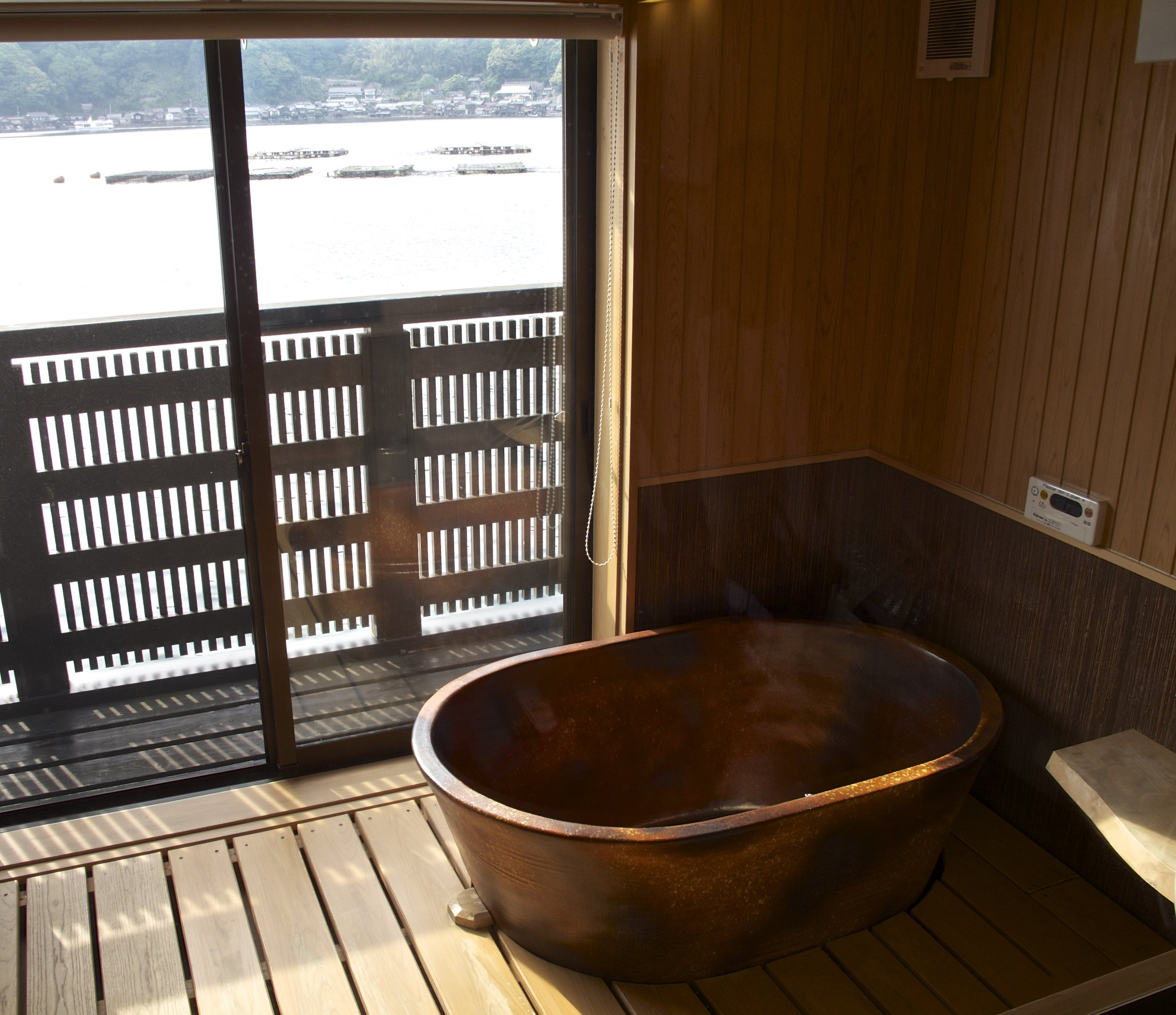 The Shigaraki stoneware bathtub at Kuraya is placed overlooking the bay so that guests can enjoy a traditional Japanese bath with a view.