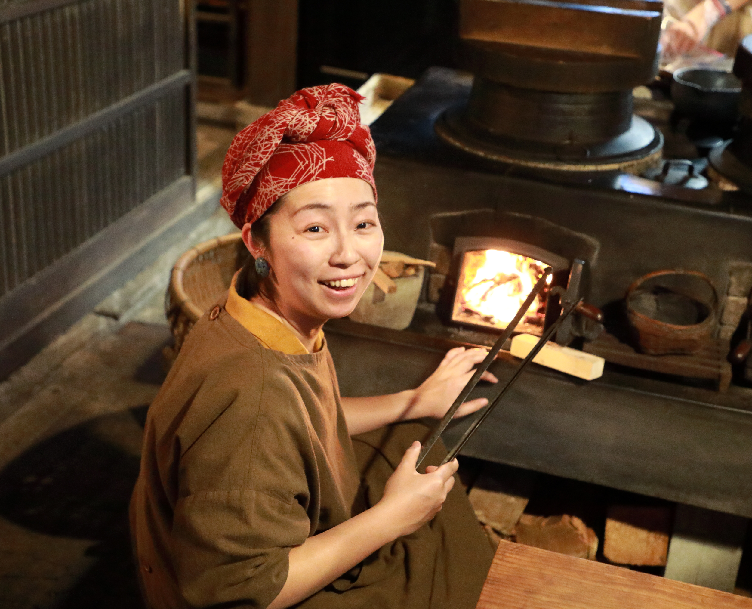Mizuho Ohkouchi, manager of Takyo Abeke, lighting the wood fire in the  kamado , or traditional wood-burning stove.