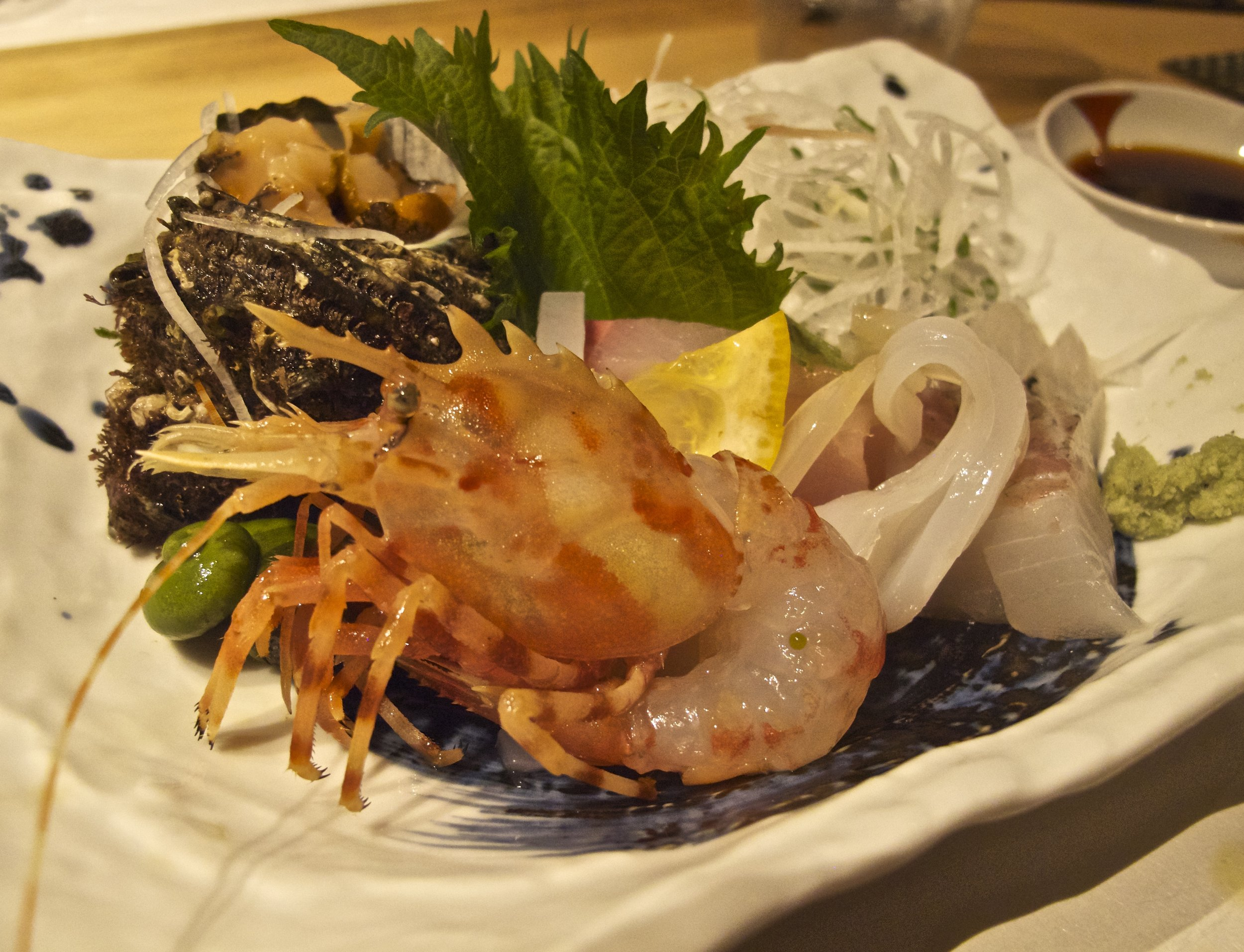 A seasonal assortment of sashimi, sliced raw fish served with your choice of soy sauce and wasabi,  sudachi  citrus juice and salt, or  yuzu kosho  as condiments. The spiked-head shrimp is a local specialty known as  aku ebi , or devil shrimp.