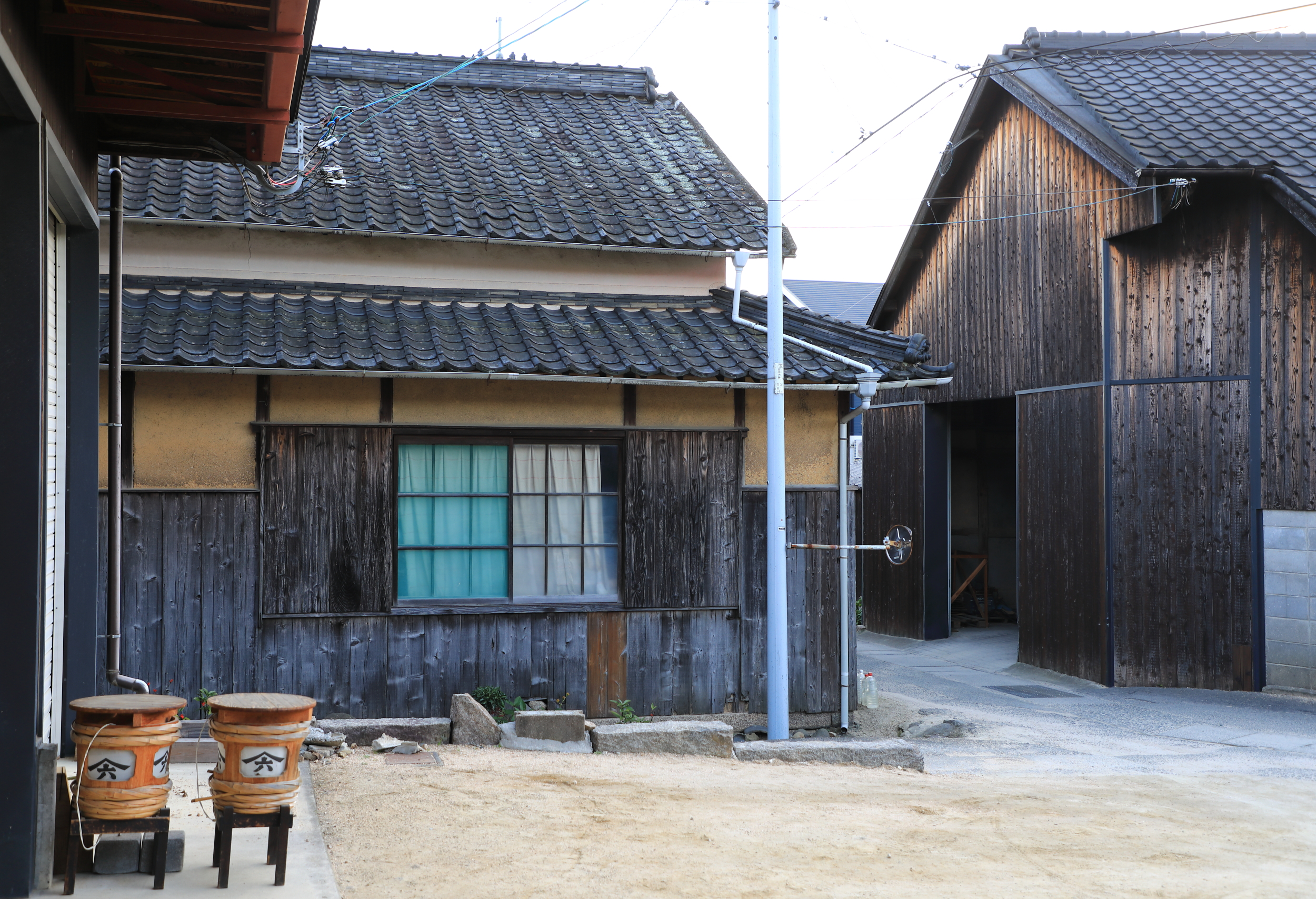 """Black walls at soy sauce breweries, like these at Yamaroku, are a sign of a prosperous business. The bacteria that create the color are the """"good"""" bacteria needed to ferment soy sauce. It also means the brewery is busy as the color immediately dissipates when business slows down or is stopped."""