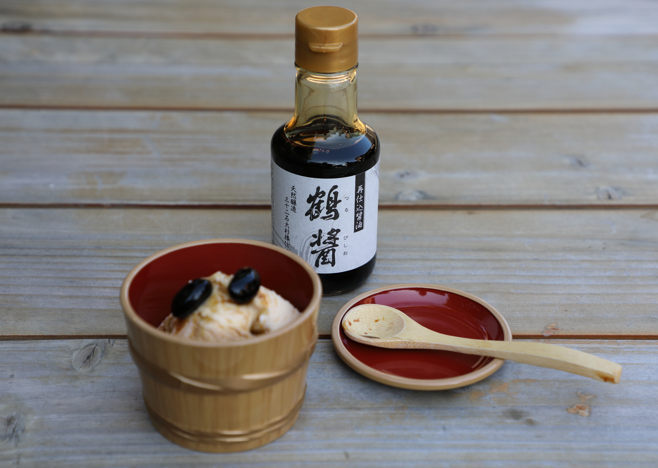 """Custard ice cream topped with Yamaroku's """"Tsuru-bishio"""" four year-aged soy sauce and large, sweet black soy beans ."""