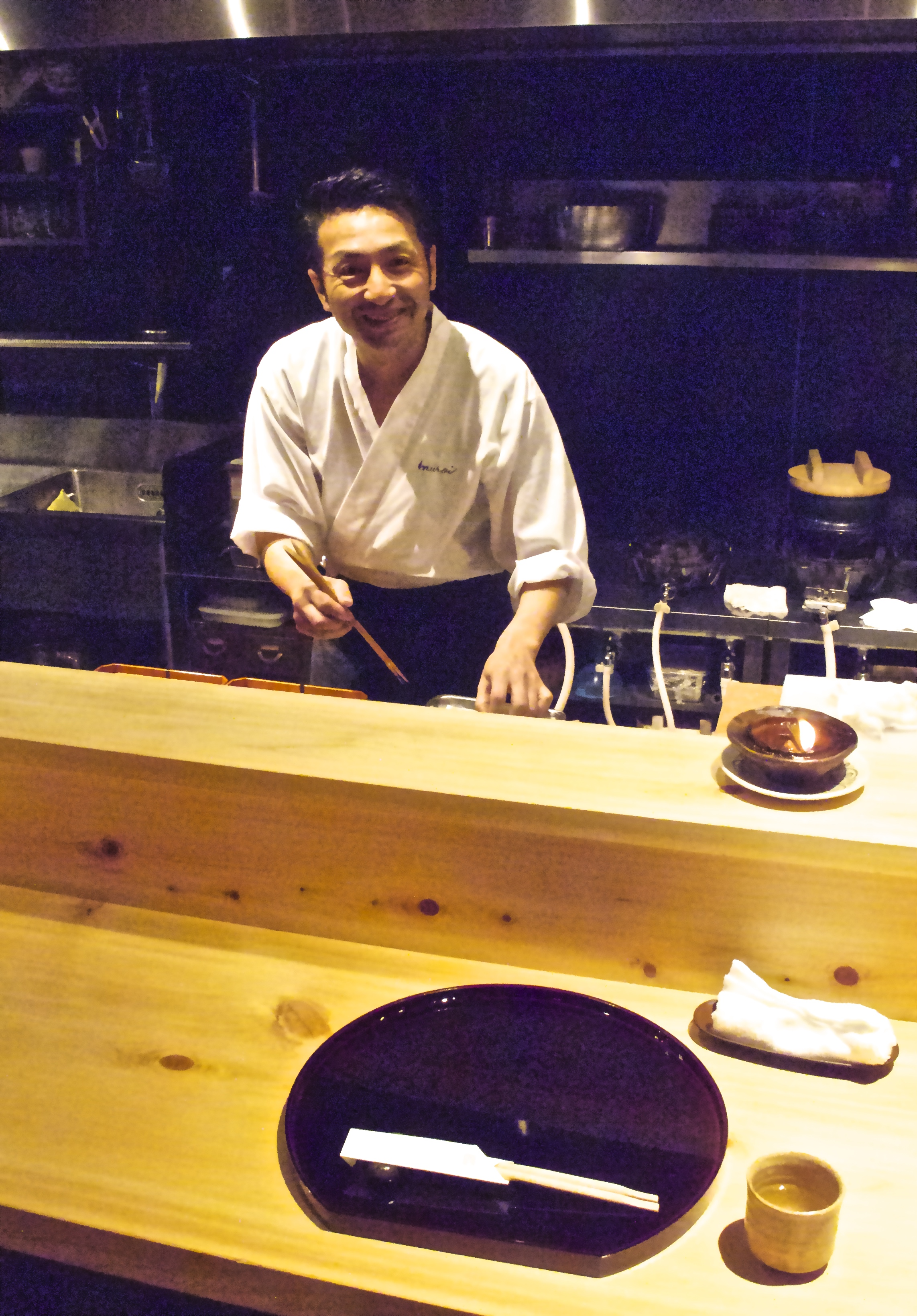 At night Shigeru is behind the counter at his restaurant preparing the meal he has devised that day.