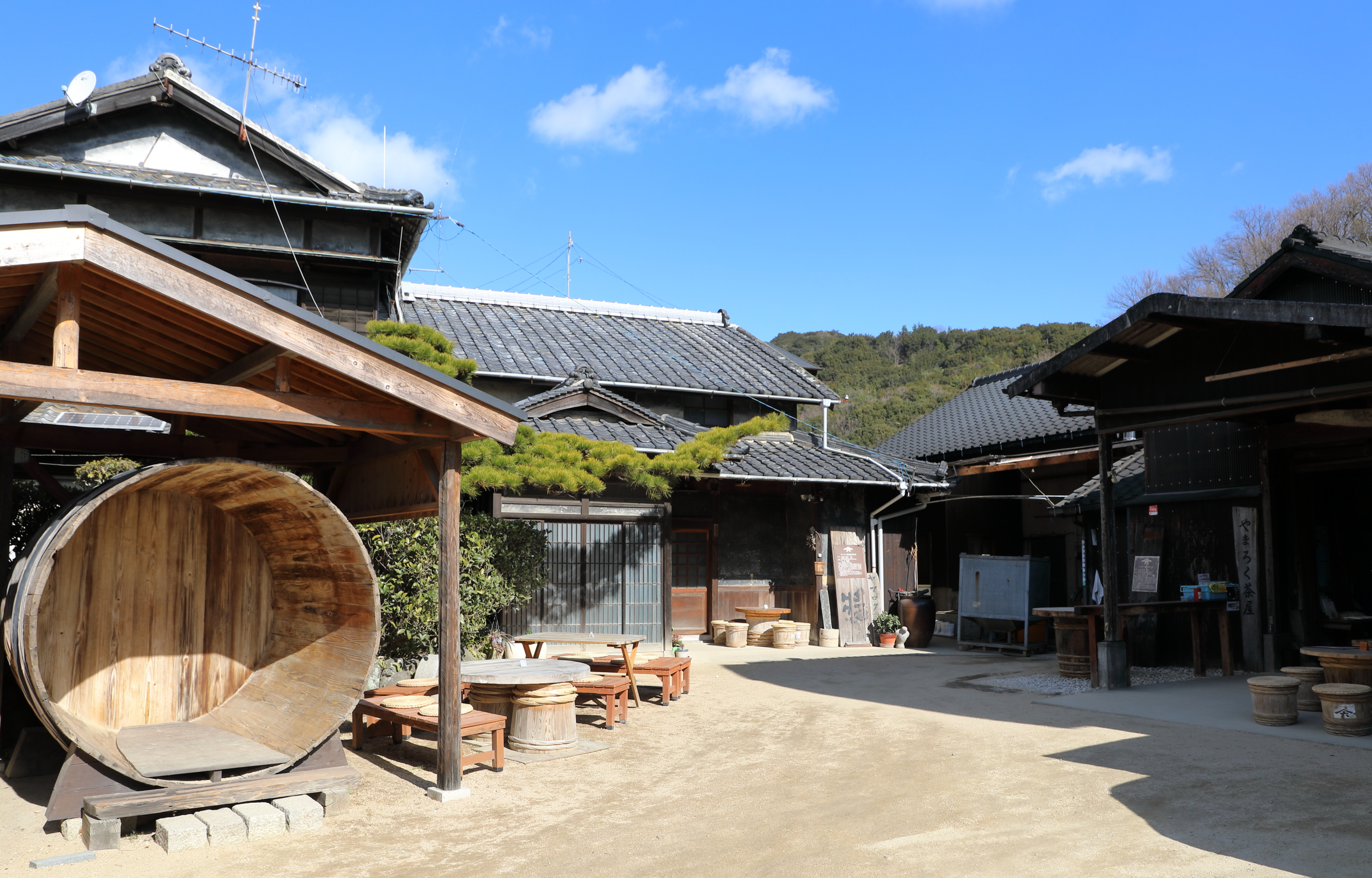 A  kioke  wooden barrel laying on its side in front of the Yamamoto family house gives visitors a sense of the large size of the barrels used to make artisanal soy sauce. The shed in which Yamaroku's soy sauce is made is on the right.