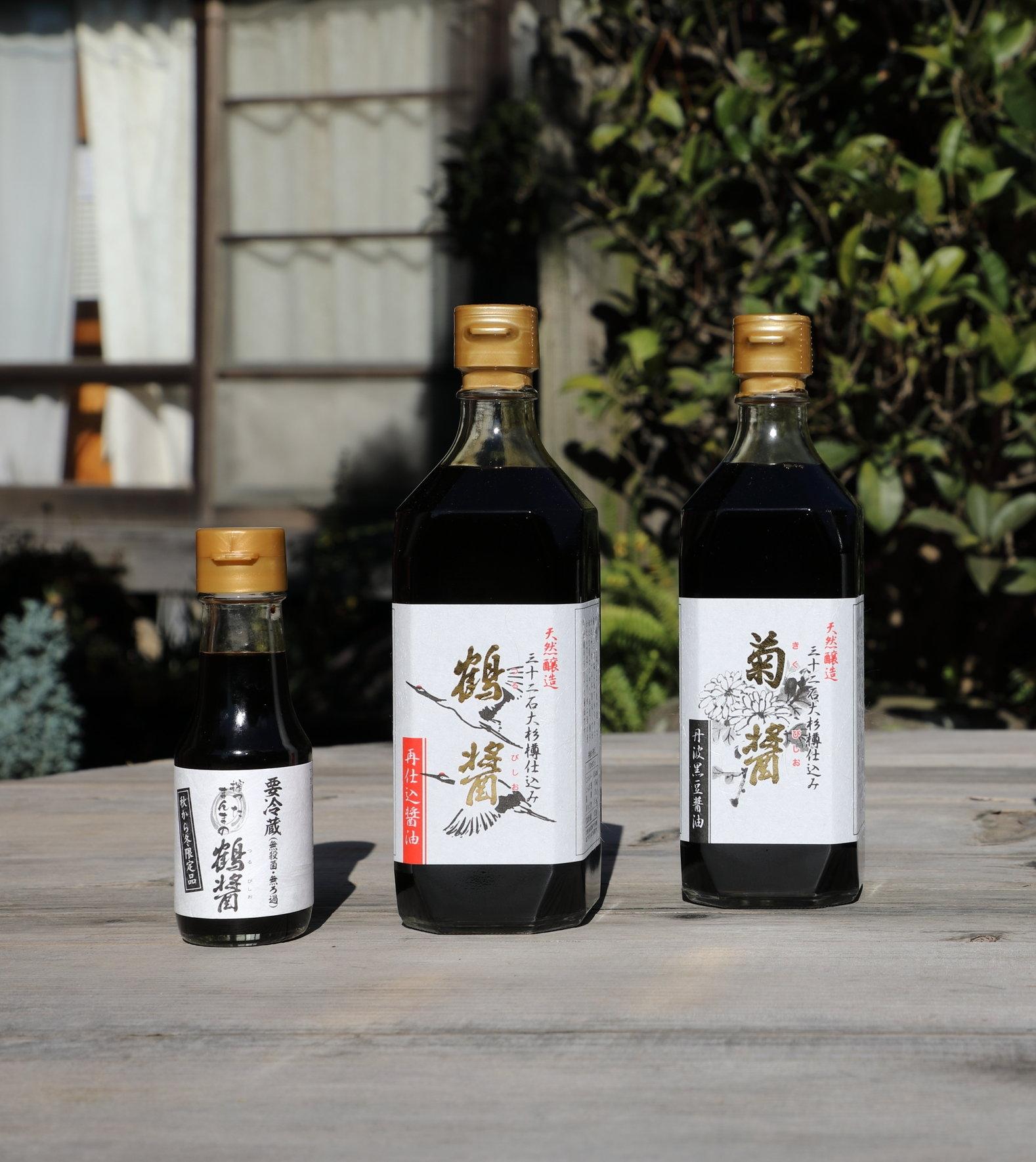 "From left to right: a small bottle of  ki-age  unpasteurized ""Tsuru-bishio""  saishikomi  soy sauce, large bottle of pasteurized  ""Tsuru-bishio""  soy sauce, and a large bottle of ""Kiku-bishio""  koikuch i soy sauce."