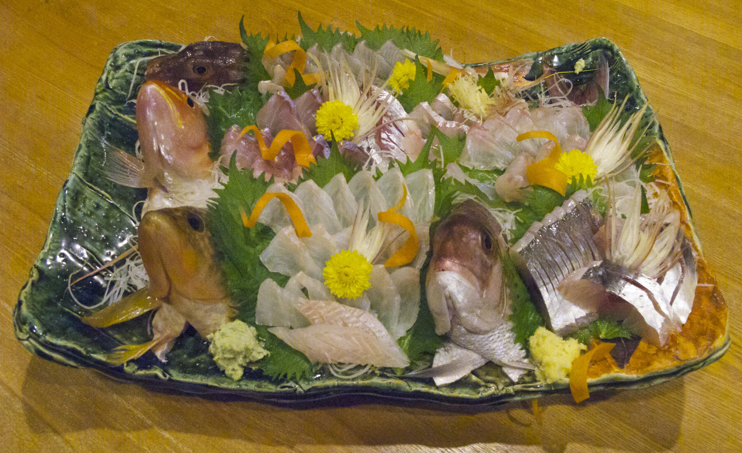 A summer platter of sashimi that includes red gunner ( hobo ), sharp-tooth snapper ( itoyori ), red-spotted grouper ( kijihata ), tilefish ( amadai ), and Japanese horse mackerel ( aji ). The still glistening eyes of the fish indicate their freshness.