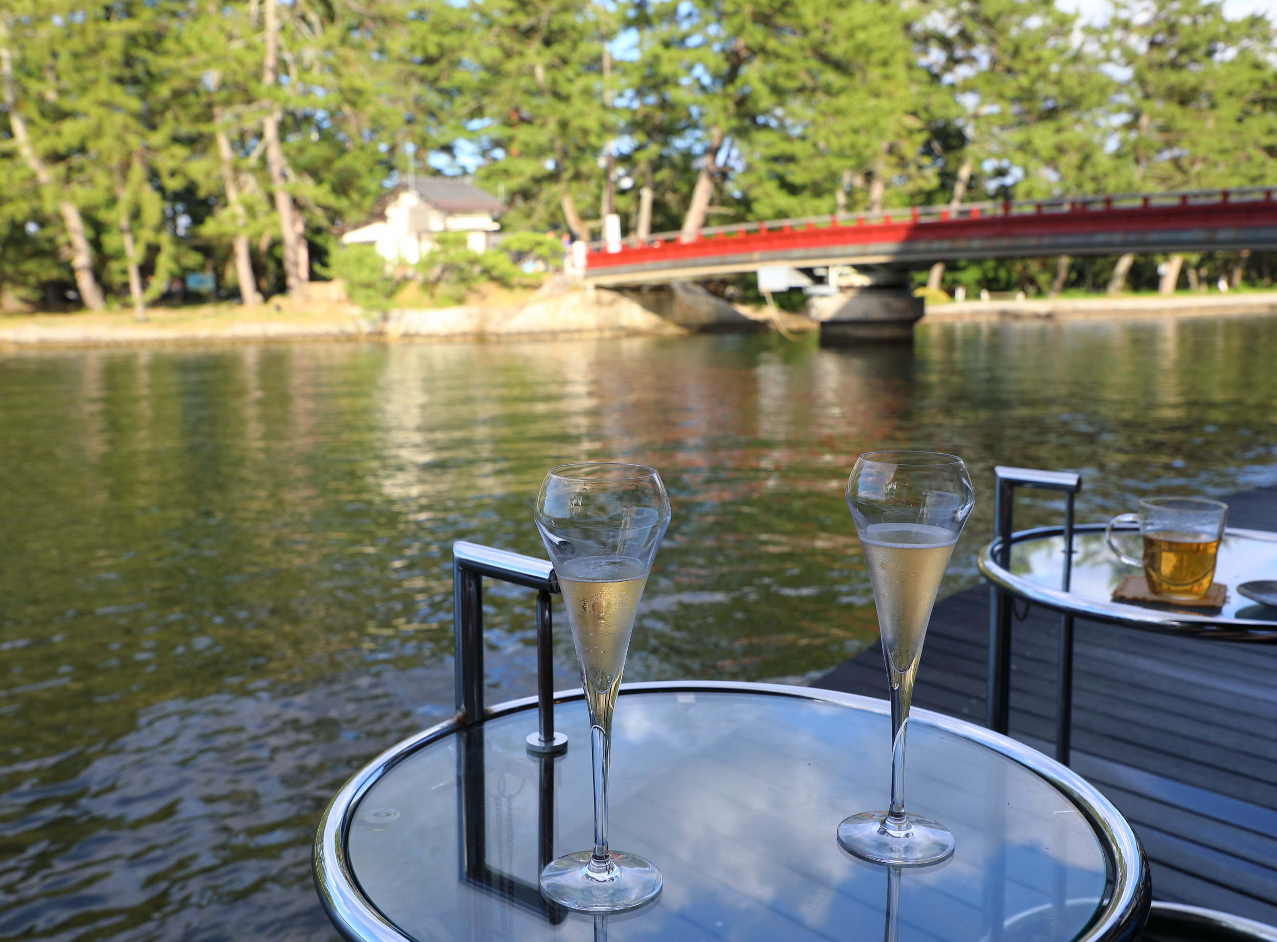 It's easy to while away an afternoon on the deck of Cafe du Pin. The red bridge across the canal connects the village of Amanohashidate to its famous pine-covered sandbar.