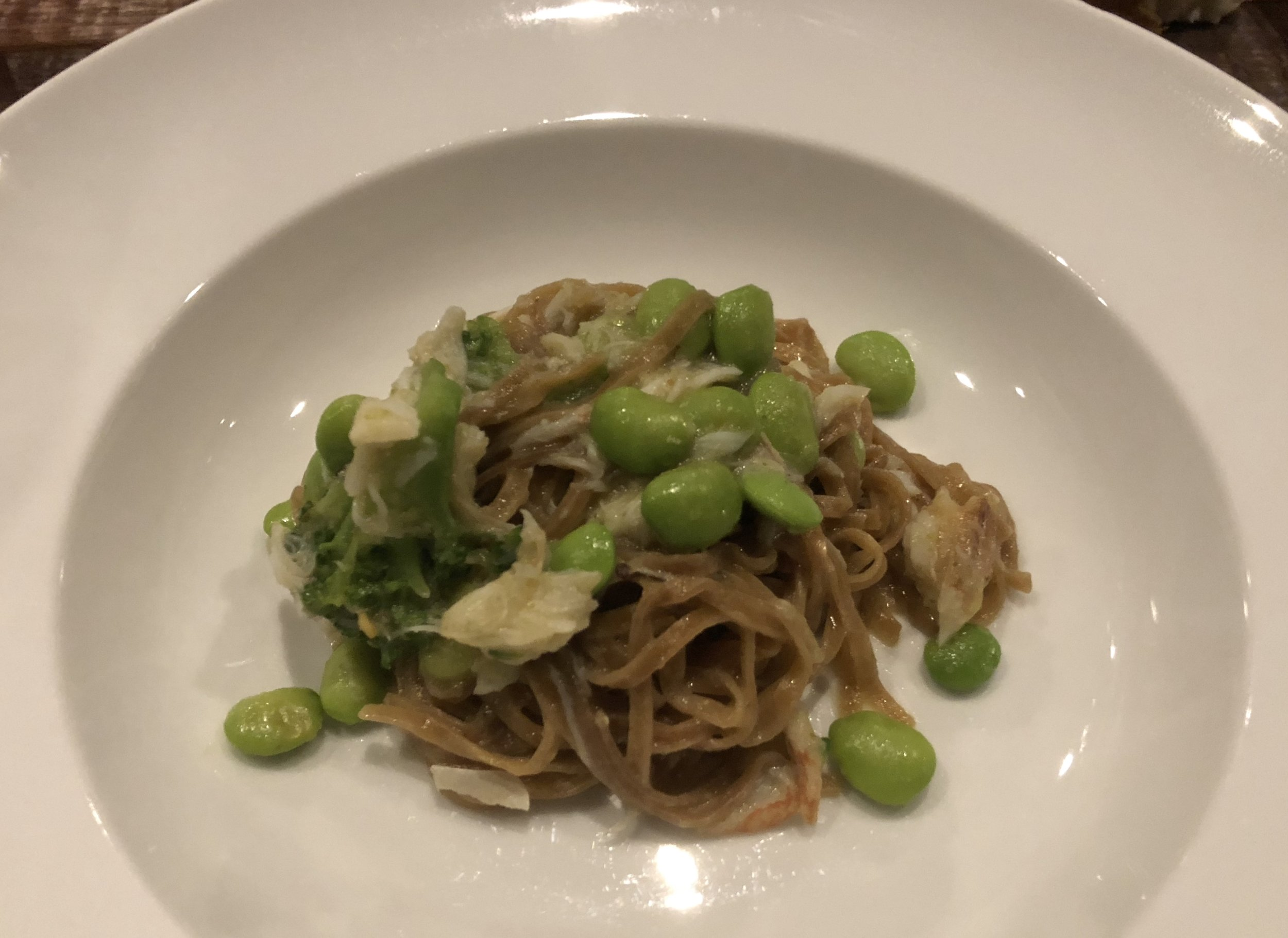 Tagliolini infused with aged sake lees and tossed with blue crab, soy beans, and broccoli.