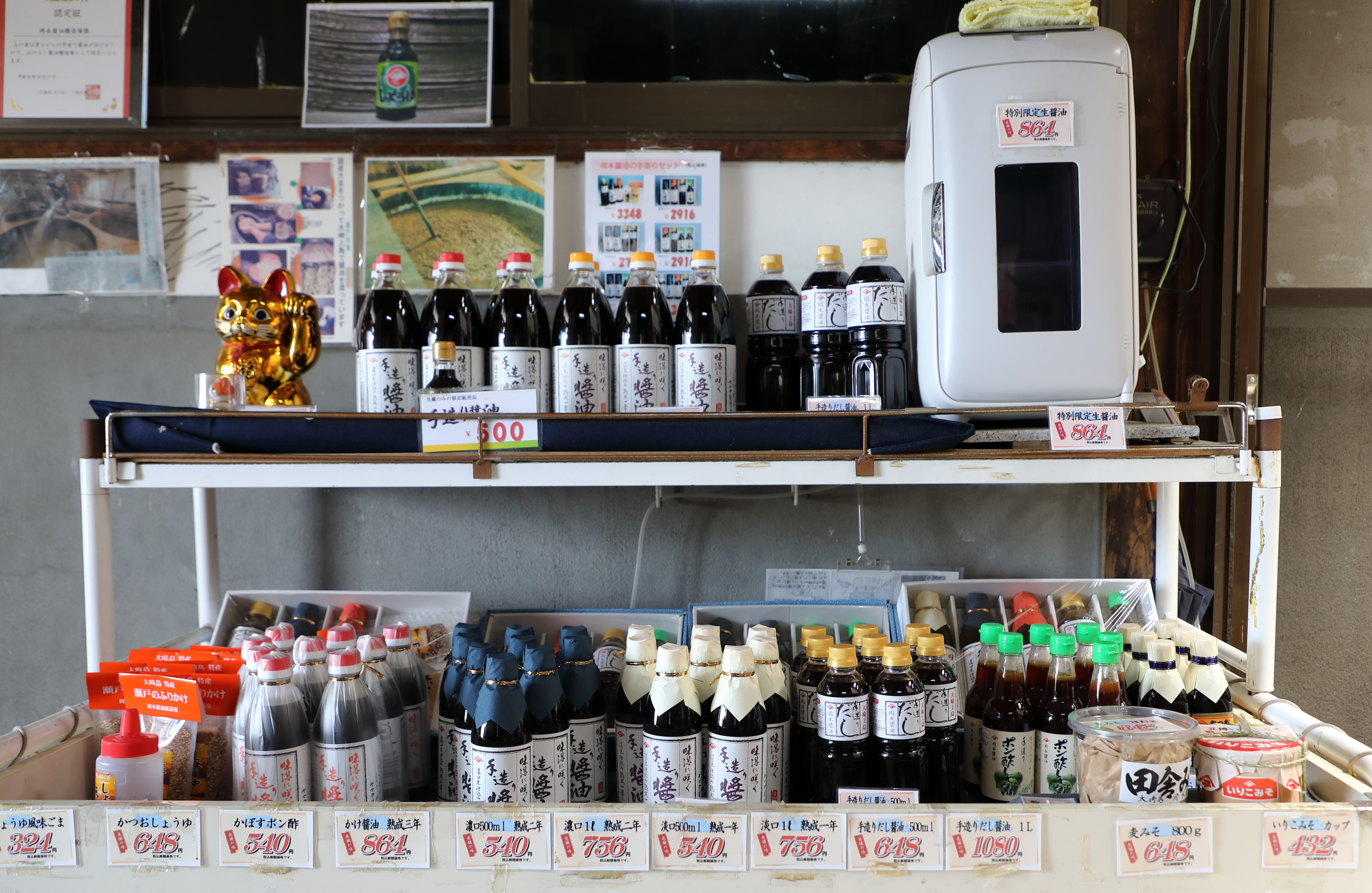 The shop at the entrance to Okamoto Shoyu, an artisanal brewer of a medium-boded classic style of soy sauce on Osaki-kamijima Island in the Seto Inland Sea. Its finishing soy sauce is unpasteurized  nama-joyu,  kept in the small white refrigerator on the right end of the upper shelf.