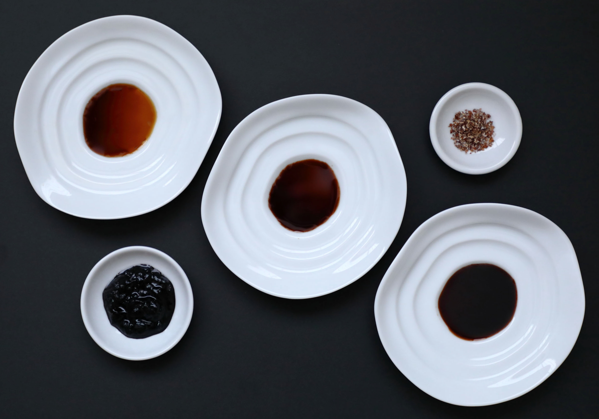 """The different styles of artisanal Japanese soy sauces made to finish foods. At the top of the diagonal is Tanakaya's refined """"Premium"""" first drip soy sauce. In the middle is Katakami's farmhouse soy sauce made with fruity green soy beans. At the bottom is Yamaroku's classic deep, rich """"Tsuru-bishio"""" soy sauce, which is fermented and aged for four years. In the small dish in the upper right hand corner is Naogen's specialty crystalized soy sauce and in the bottom left hand corner Sawai's chunky soy sauce.  The large soy sauces dishes along the diagonal are among a variety of shapes being made to help people better use and appreciate artisanal Japanese soy sauce. Similar to ink stones used in calligraphy, the sloped design prevents people from pouring too much soy sauce by creating a small shallow pool at the center. The sloped sides help prevent using too much soy sauce when dipping and dragging food along them, while also enabling one to better see the soy sauce's true beautiful colors. Such dishes are also convenient chopstick rests."""