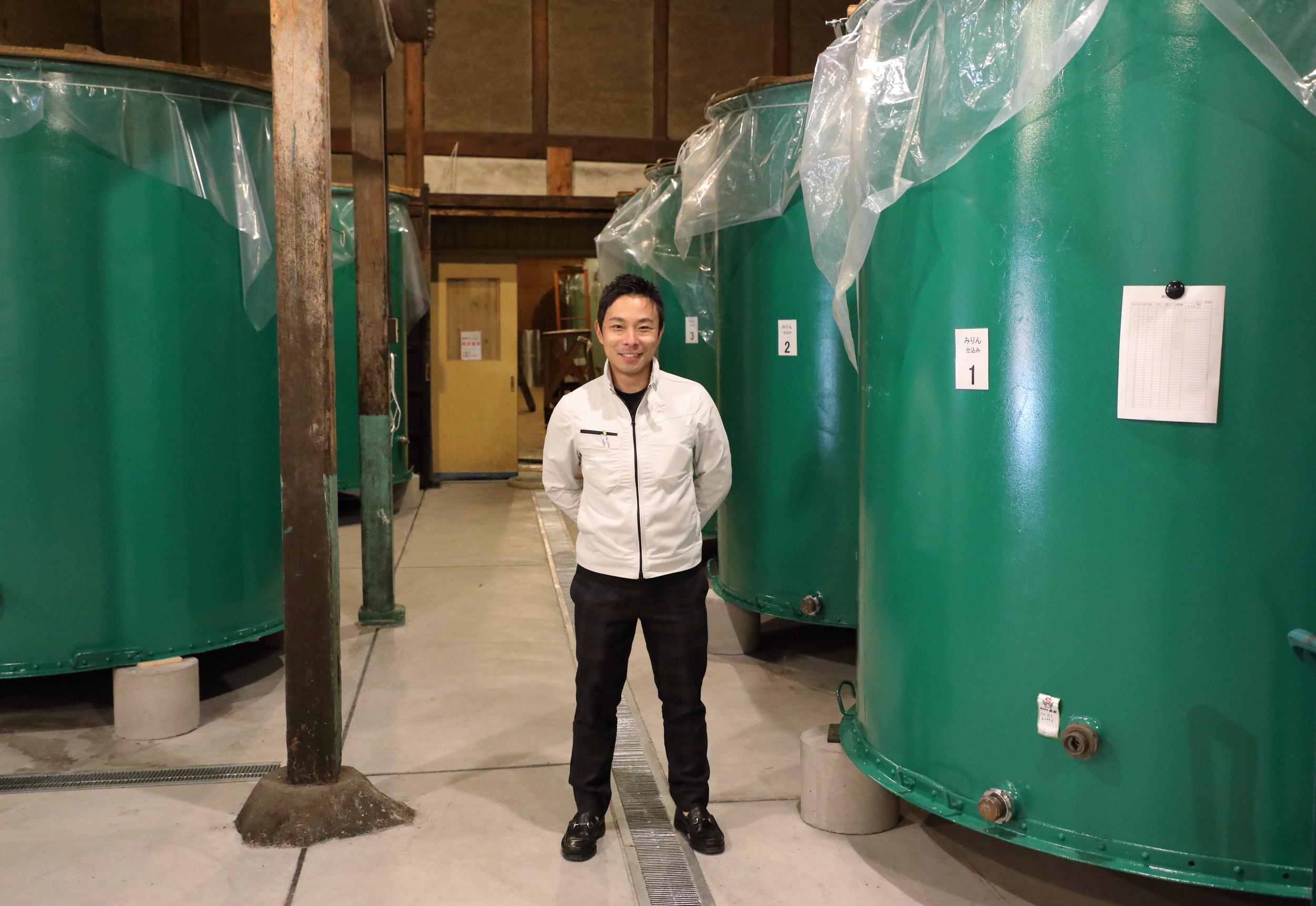 The fifth generation head of Hakusen Shuzo, Yuki Kato standing amidst the tanks used to ferment  hon-miri n.