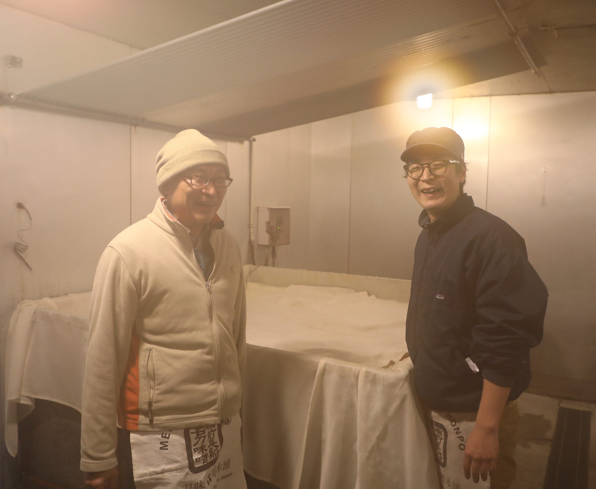 From right to left: Yohei Meitou with his father Noritaka Meitou in their sauna-like  muro  room during the first day of culturing a batch of white rice into koji.