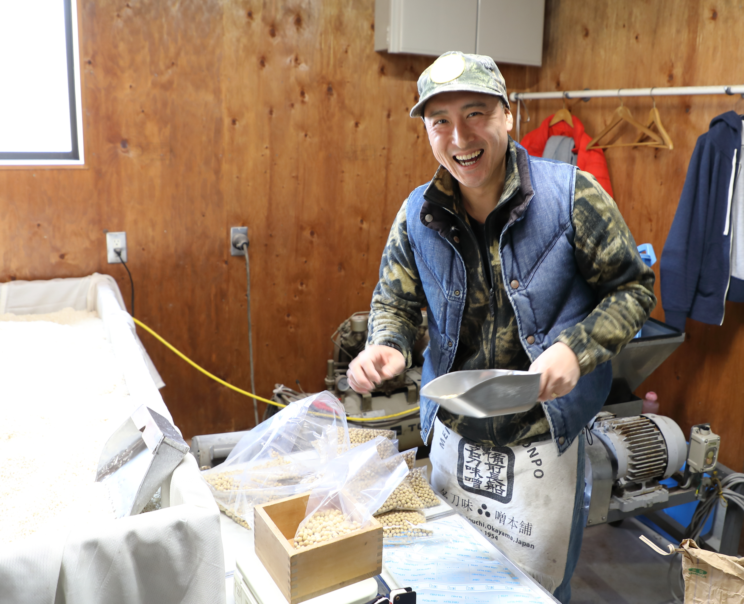 Ryuhei Meitou packing bags of dry soy beans to provide customers with all of the ingredients they need to make miso at home.