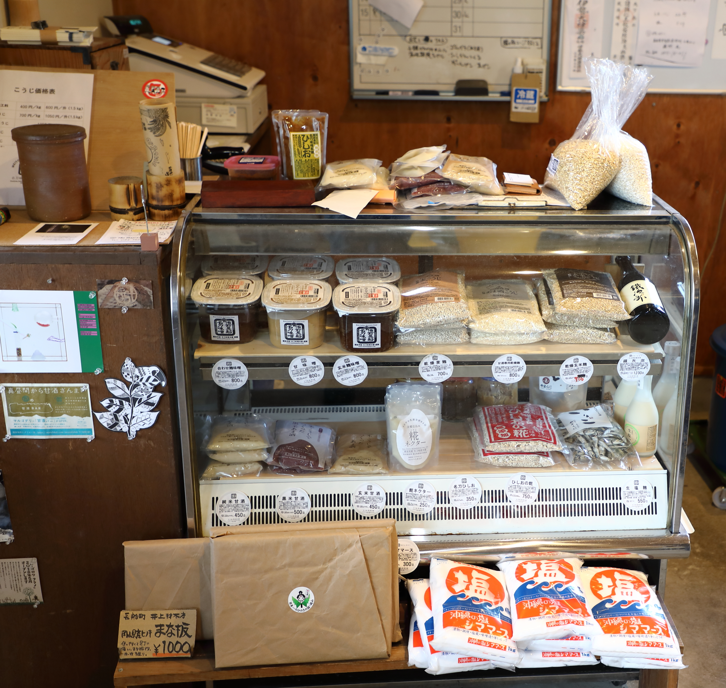 A refrigerator case of Meitou's fresh miso, koji, amazake, and other products at the entrance to the workshop.