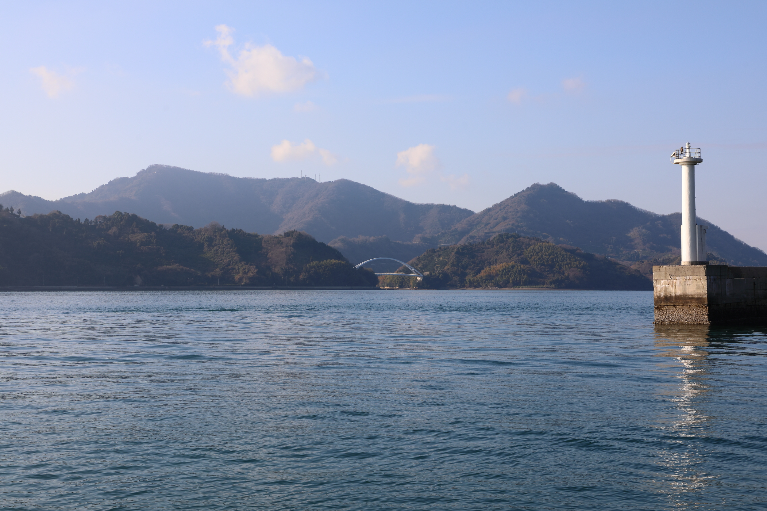 Seen from a ferry stop on neighboring Osakikamijima Island, the entrance to Osakishimojima's main harbor is under the bridge that connects two small islands located just in front of the island.