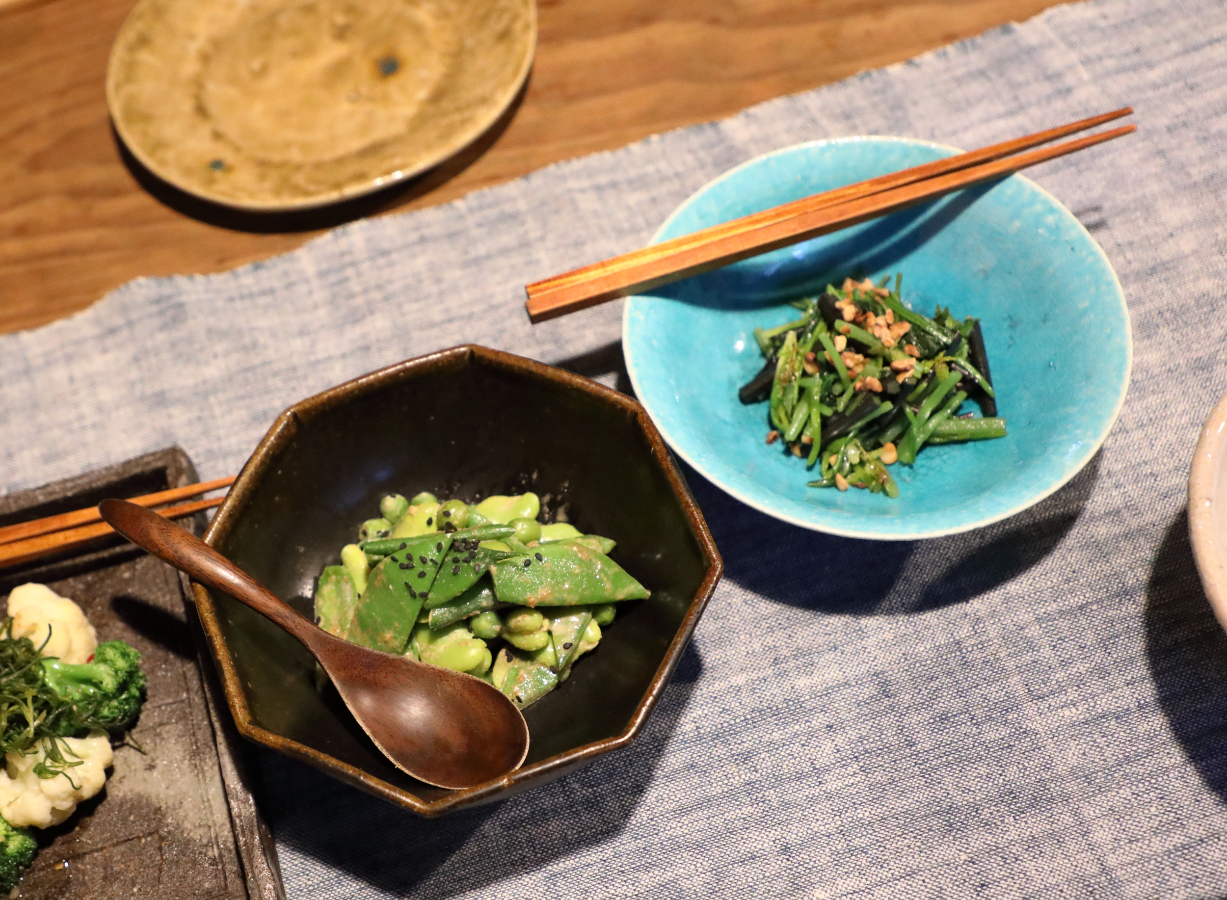 In the top right blue bowl is  horenso ohitashi , which is spinach lightly pickled in sake and soy sauce overnight and topped with toasted sesame seeds. In the bottom left black bowl is  mame goma-ae , a medley of spring beans and peas coated with an earthy sauce made of ground toasted sesame seeds, sake, soy sauce, and sugar.