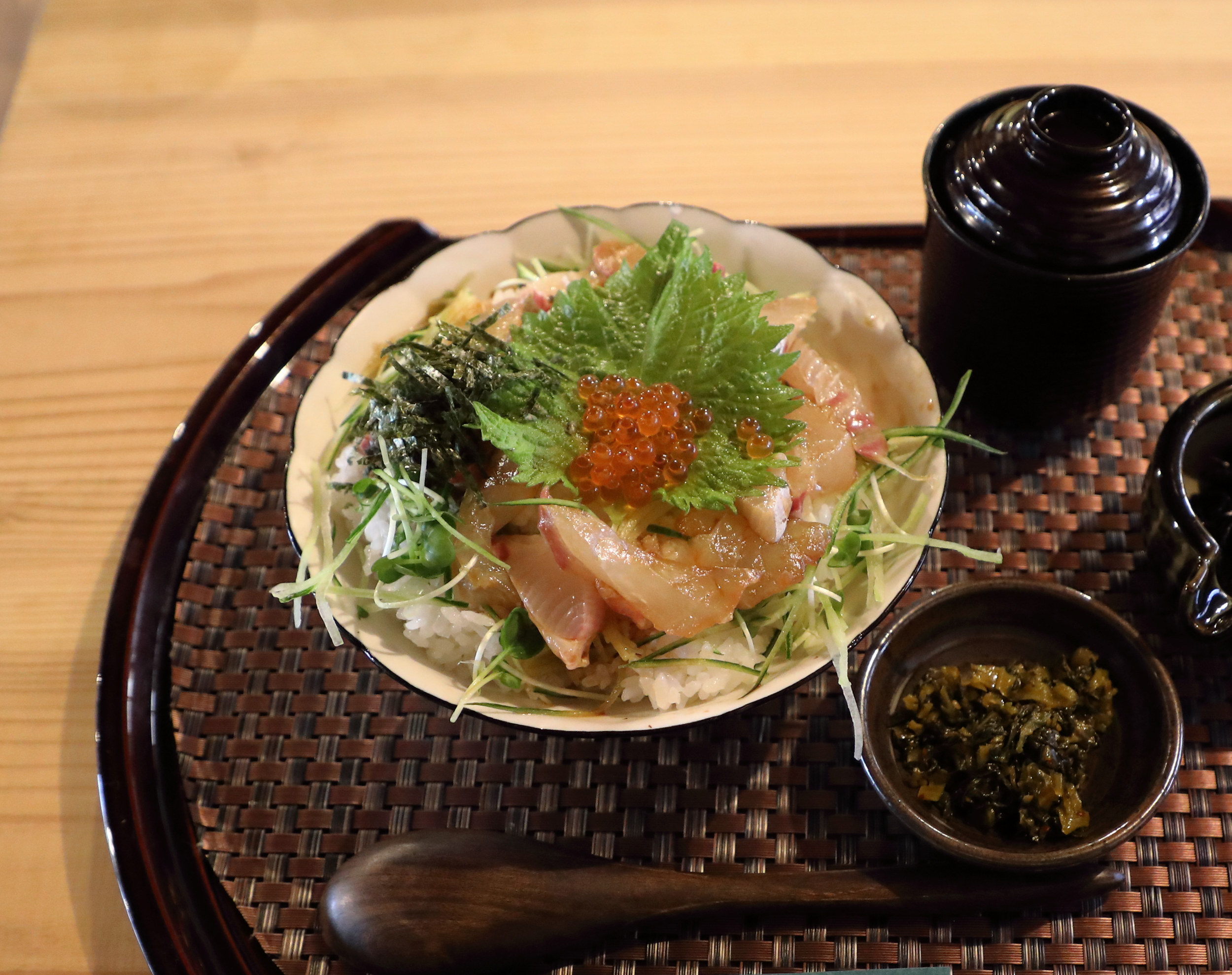 Freshly-caught sea bream ( tai ) is lightly marinated in sake and soy sauce before being served on a bed of delicately sweet sushi rice and garnished with peppery  kaiware  sprouts, salty  nori  seaweed strips, a minty  shiso  leaf, and creamy  ikura  salmon roe.
