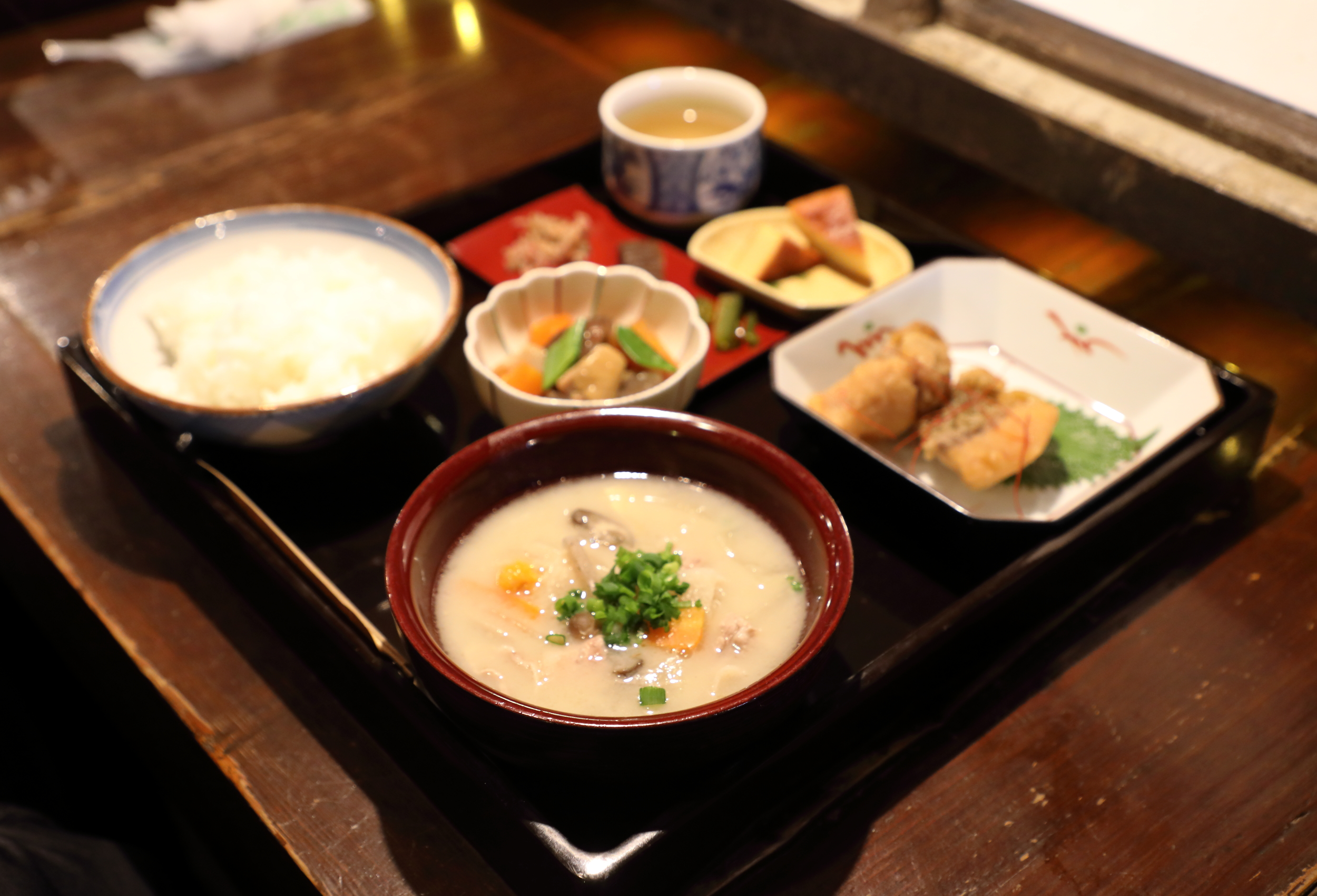 In the brown bowl  kasu-jiro  is a rich, slightly sweet stew made with  sake kasu  and either pork or salmon and vegetables.