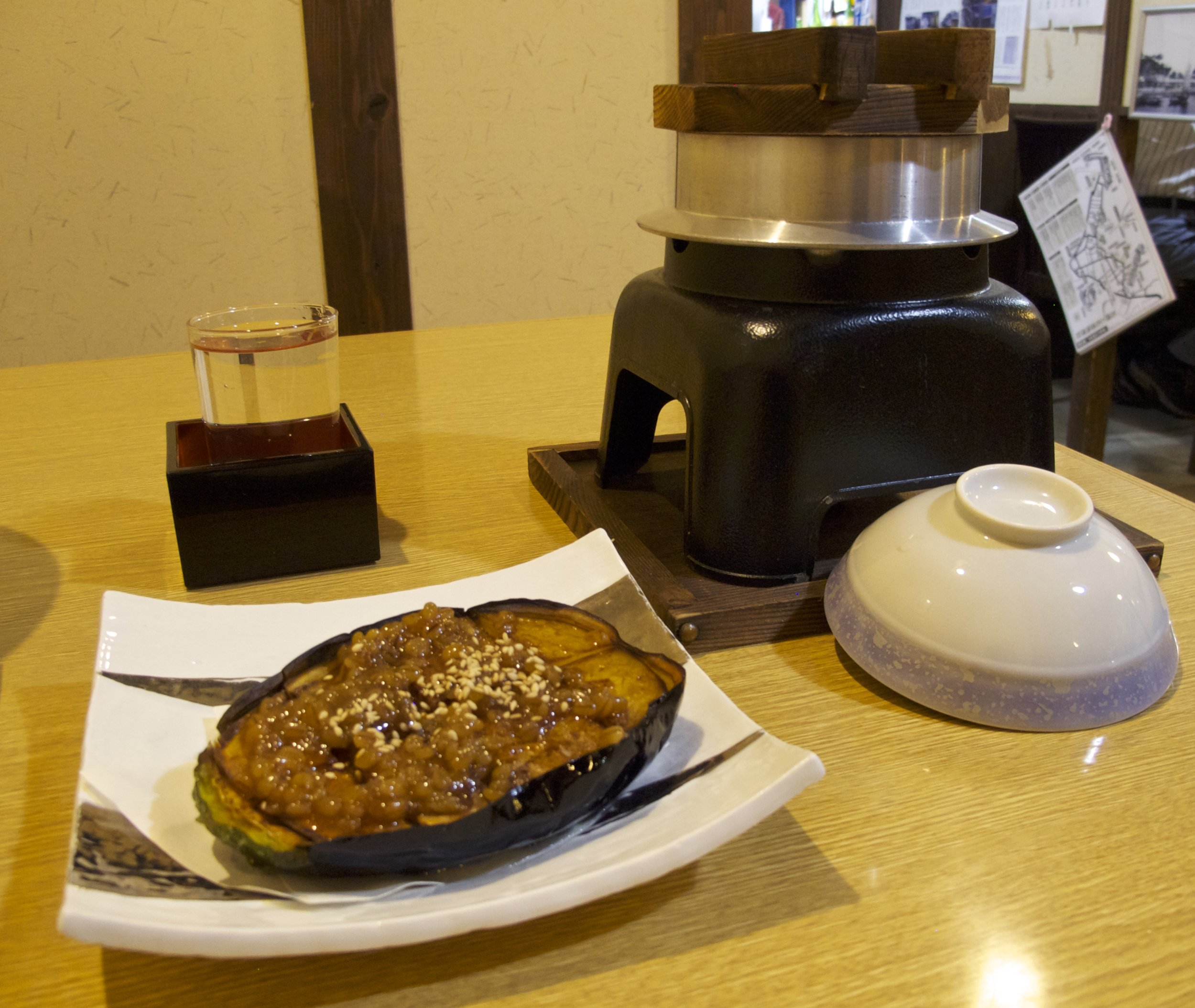 A glass of sake served alongside n asu dengaku , which is a roasted eggplant that has been glazed with a sauce made of sake, miso,  hon-mirin , and sugar. The sauce can also be used to glaze tofu, fish, and vegetables.
