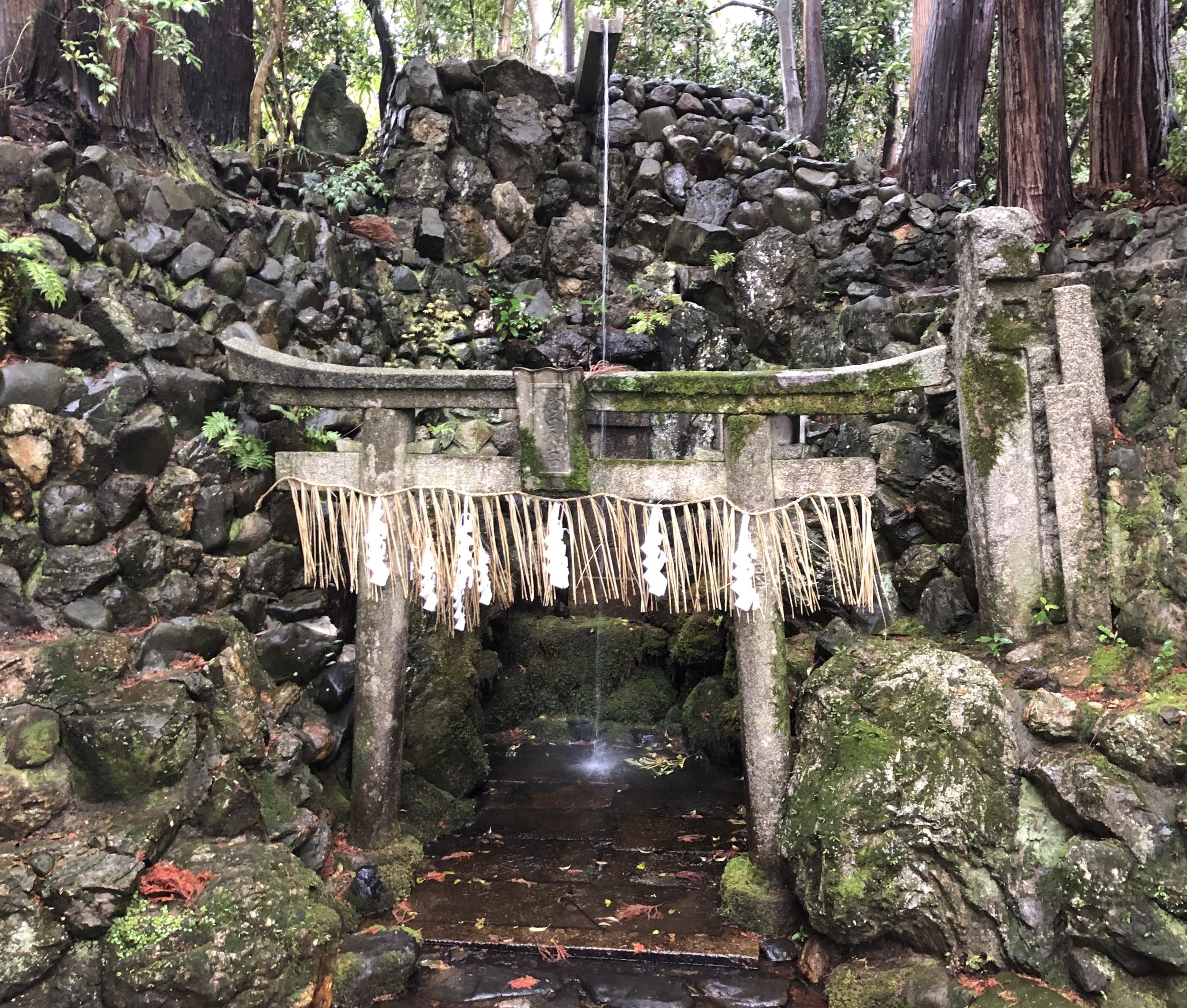 A sacred water spout in the hills behind Kyoto city marked by a stone Shinto  torii  gate and  shimenawa  of woven rice straw.