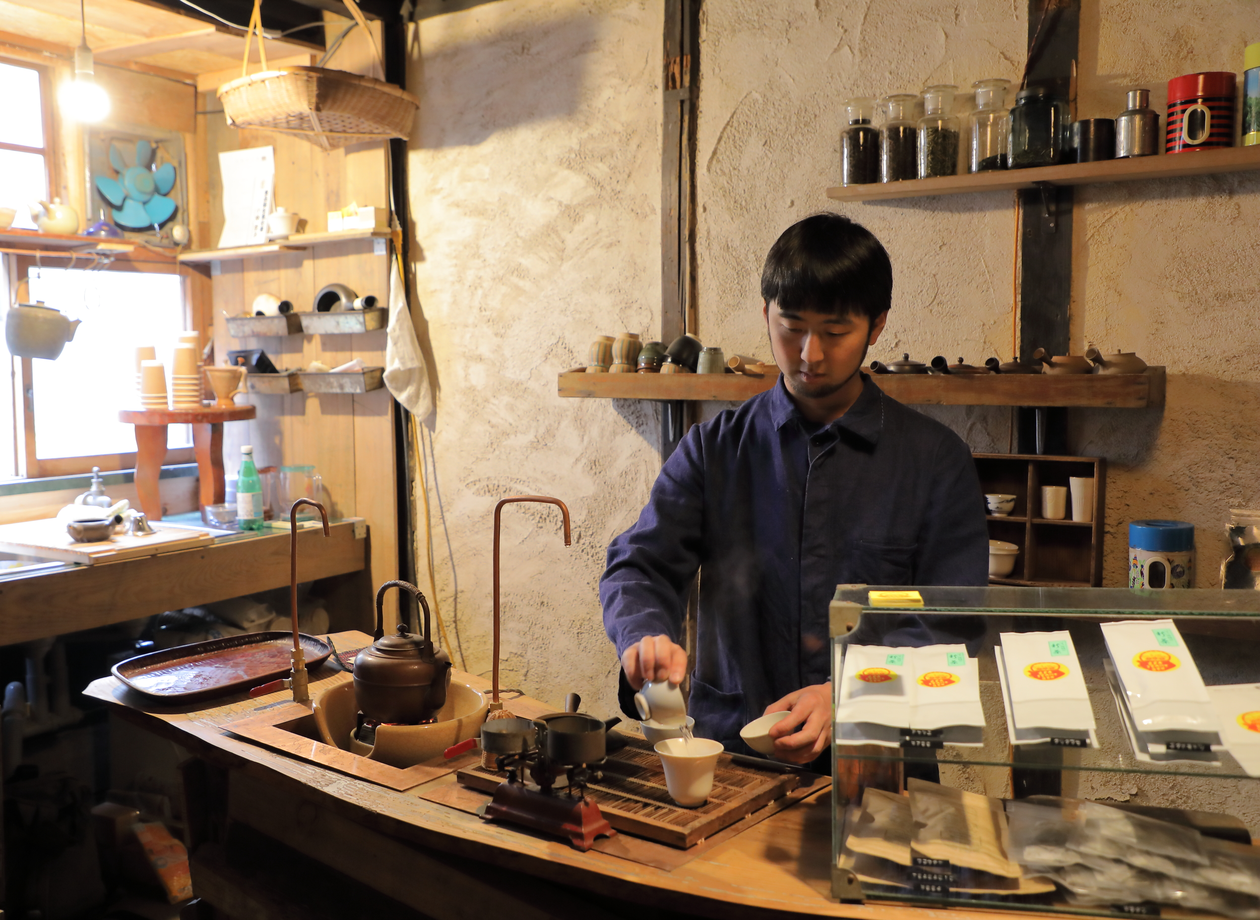 Genki Takahashi heating the tea cups and cooling the water in preparation to brew the first of a series of cups of  sencha  at Tea Stand Gen.