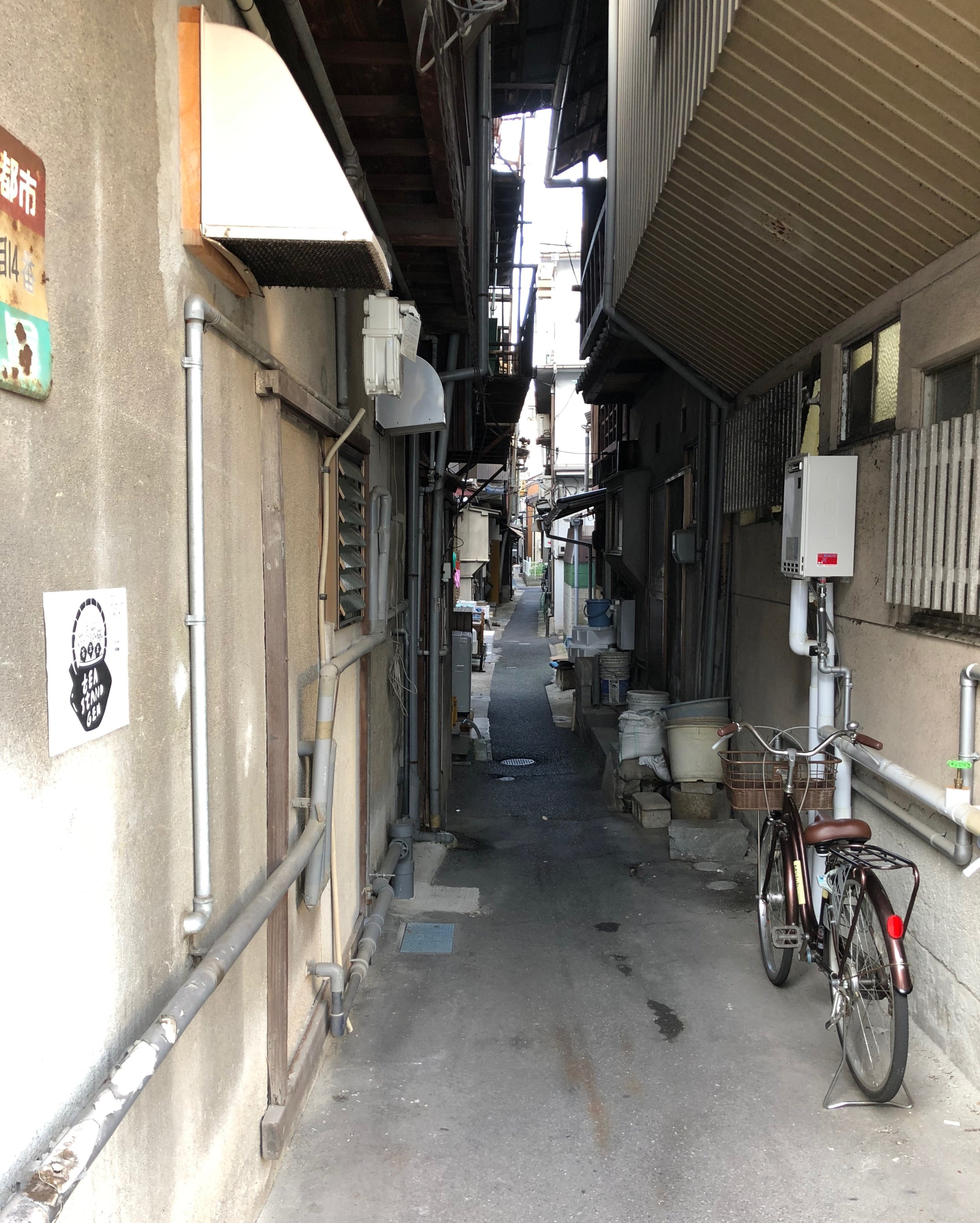 The black and white sign with Tea Stand Gen's logo on the left wall helps visitors find the narrow lane on which the shop is located in the warren of streets of the old port area of Onomichi.