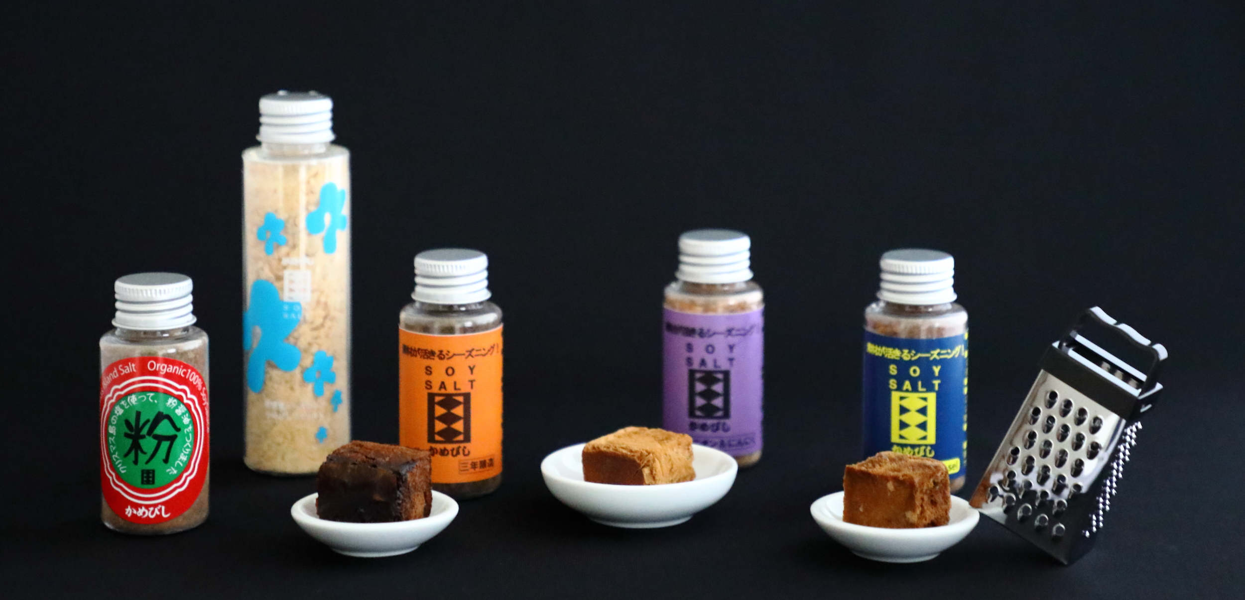 """One of Kamebishiya's modern innovations is freeze-dried soy sauce, called soy salts, which come in a powdered form in bottles and cubes that can be grated as used. From the left: a powdered soy sauce made with mineral-rich sea salt from Christmas Island, a tall bottle of powdered  usukuchi  soy sauce, three-year soy sauce in powdered and cube forms, onion and garlic-flavored soy sauce in powdered and cube forms, and """"super sel"""" soy sauce in powdered and cube forms that have been fortified with extra salt."""