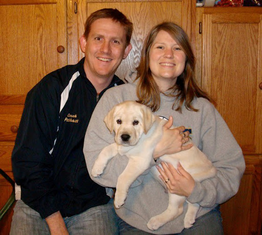 Mike with his wife Sarah and Rufus as a puppy.
