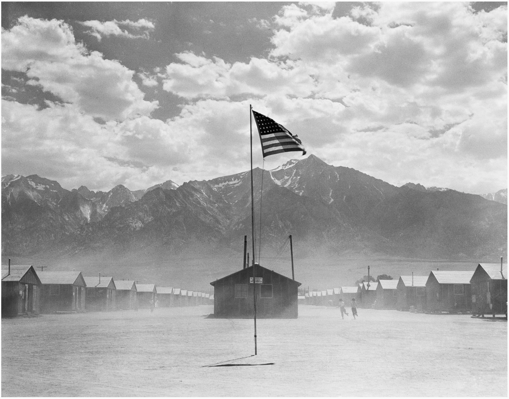 Dorothea Lange; July 3, 1942, Manzanar, California  Original caption: Manzanar, California. Dust storm at this War Relocation Authority center where evacuees of Japanese ancestry are spending the duration.    Copyright: This image is public domain as a work of the United States federal government.