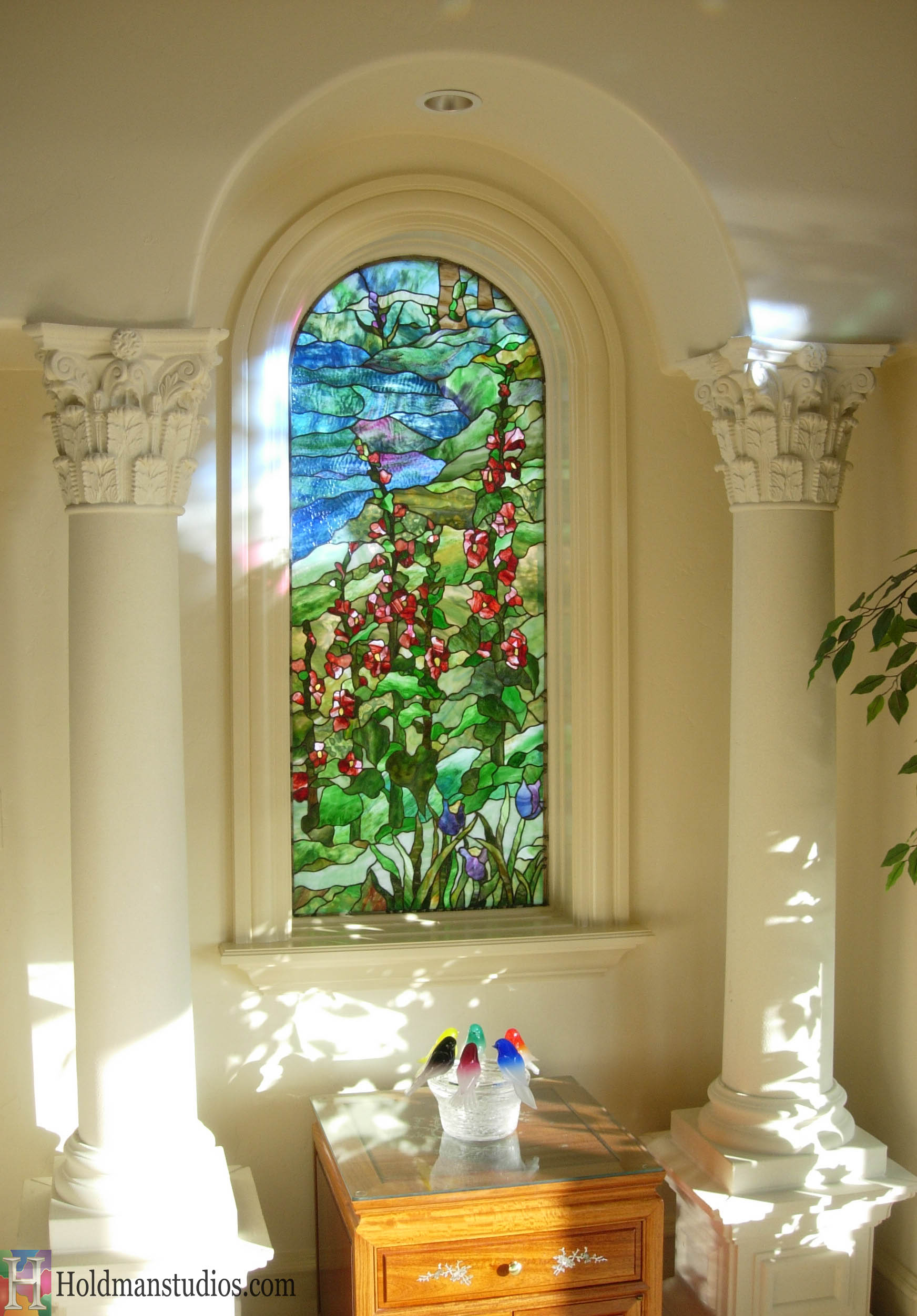 Stained Glass side Bedroom window with trees, river water, flowers, grass, mountains, and clouds in the sky.Created by artists under the direction of Tom Holdman at Holdman Studios.