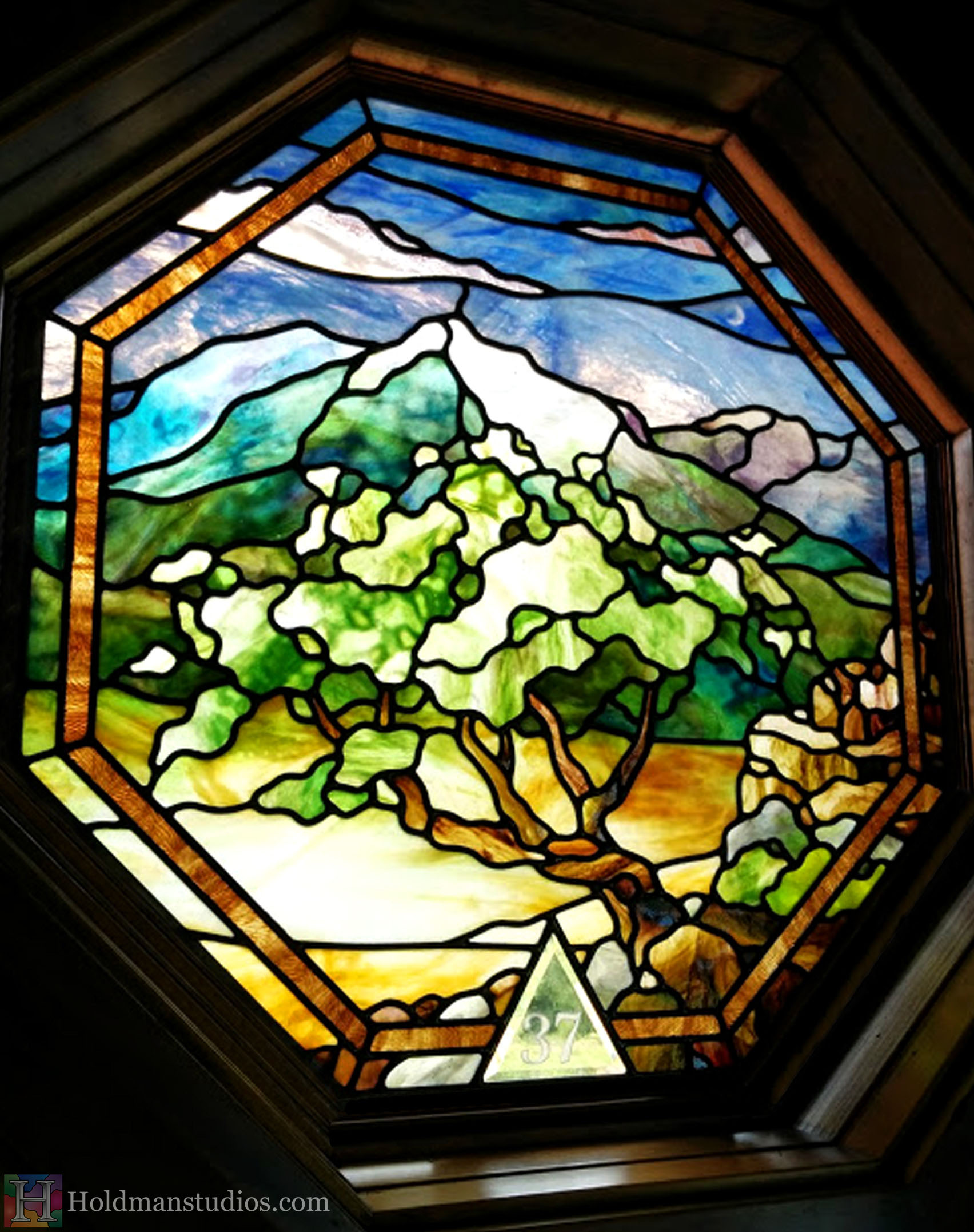 Octagon stained glass window of the sky with clouds, mountains, cliffs, trees,flowers, plants, rocks and leaves.Created by artists under the direction of Tom Holdman at Holdman Studios.