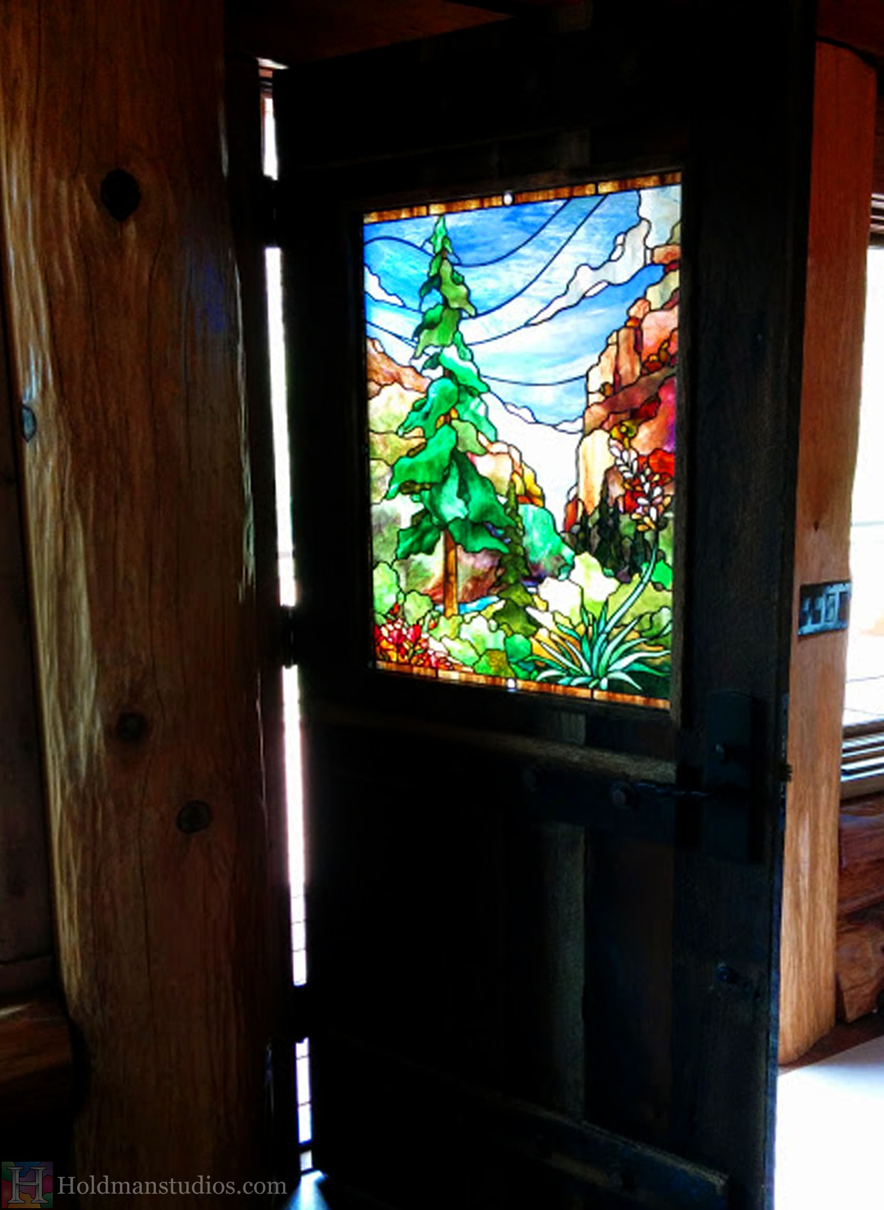 Stained glass front door window of the sky with clouds, mountains, pine trees,flowers, plants, and leaves.Created by artists under the direction of Tom Holdman at Holdman Studios.