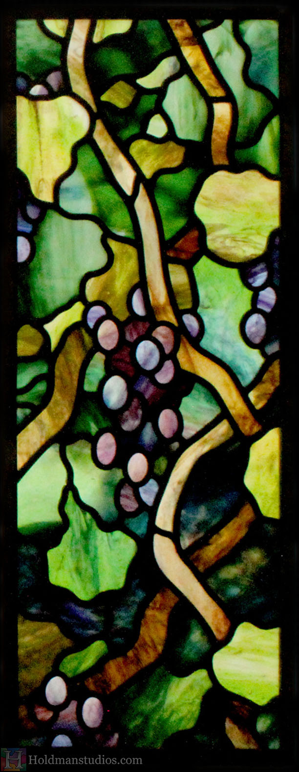 Stained glass kitchen cabinet window of vines, leaves, blossoms, and grapes. Created by artists under the direction of Tom Holdman at Holdman Studios